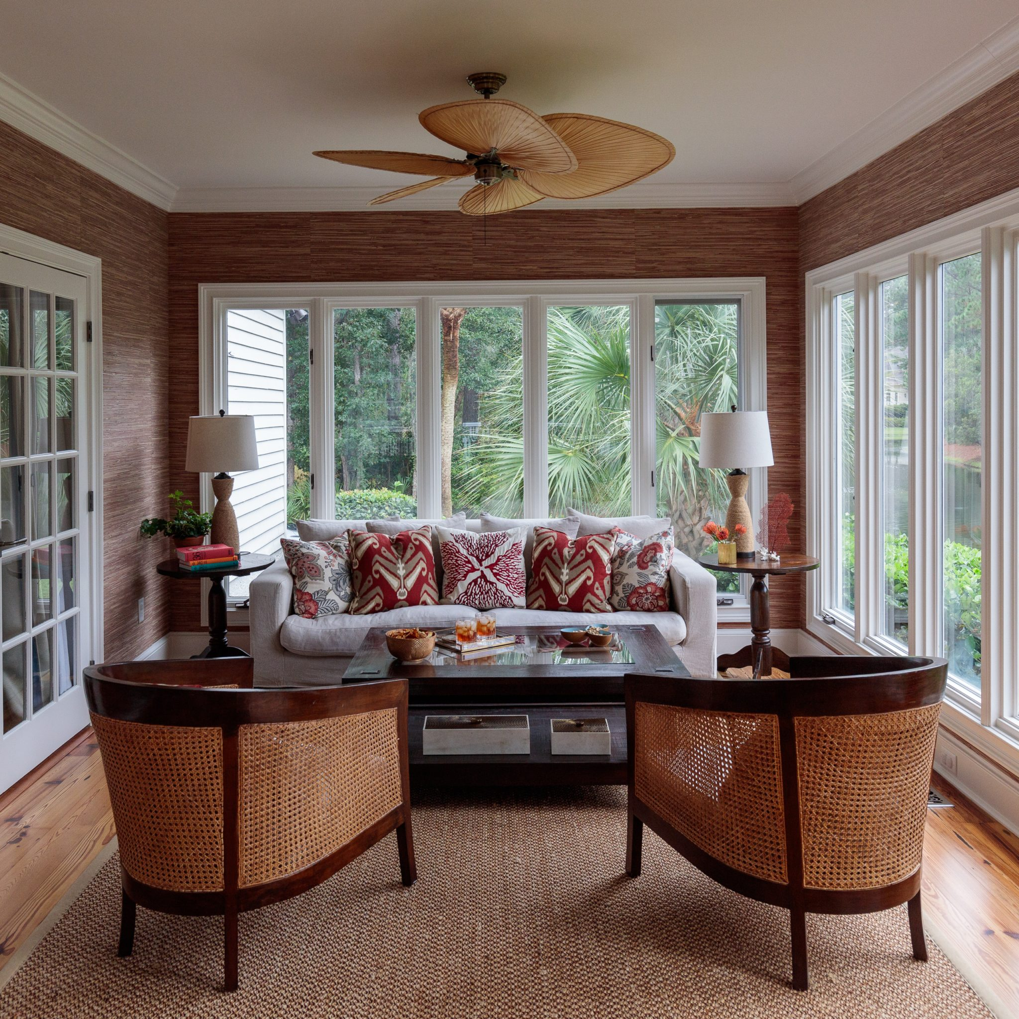 Seagrass walls, cane chairs and bamboo fan bring coastal glam to the sunroom by J Banks Design