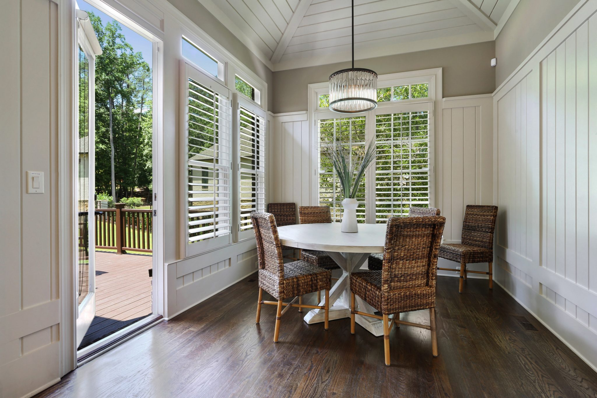 White paneling and accent rattan chairs make for a stunning breakfast nook by BJS Assoc Interior Design