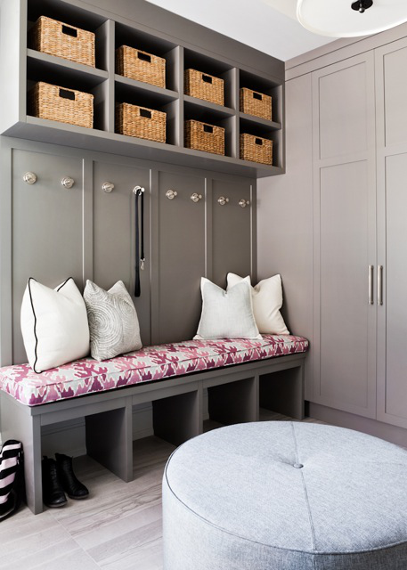 A bright Kelly Wearstler printed linen fabric adds a fun pop of color to the warm taupe tones of the mudroom, which is both stylish and functional with custom-built cabinetry and storage.