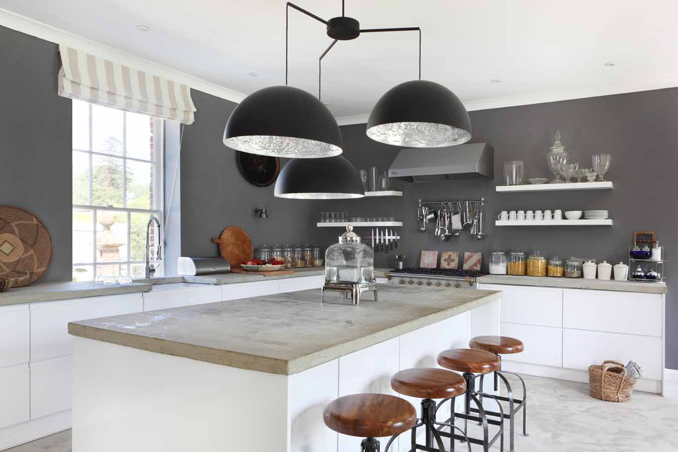 Open plan white kitchen in a converted stable featuring concrete top by VSP Interiors