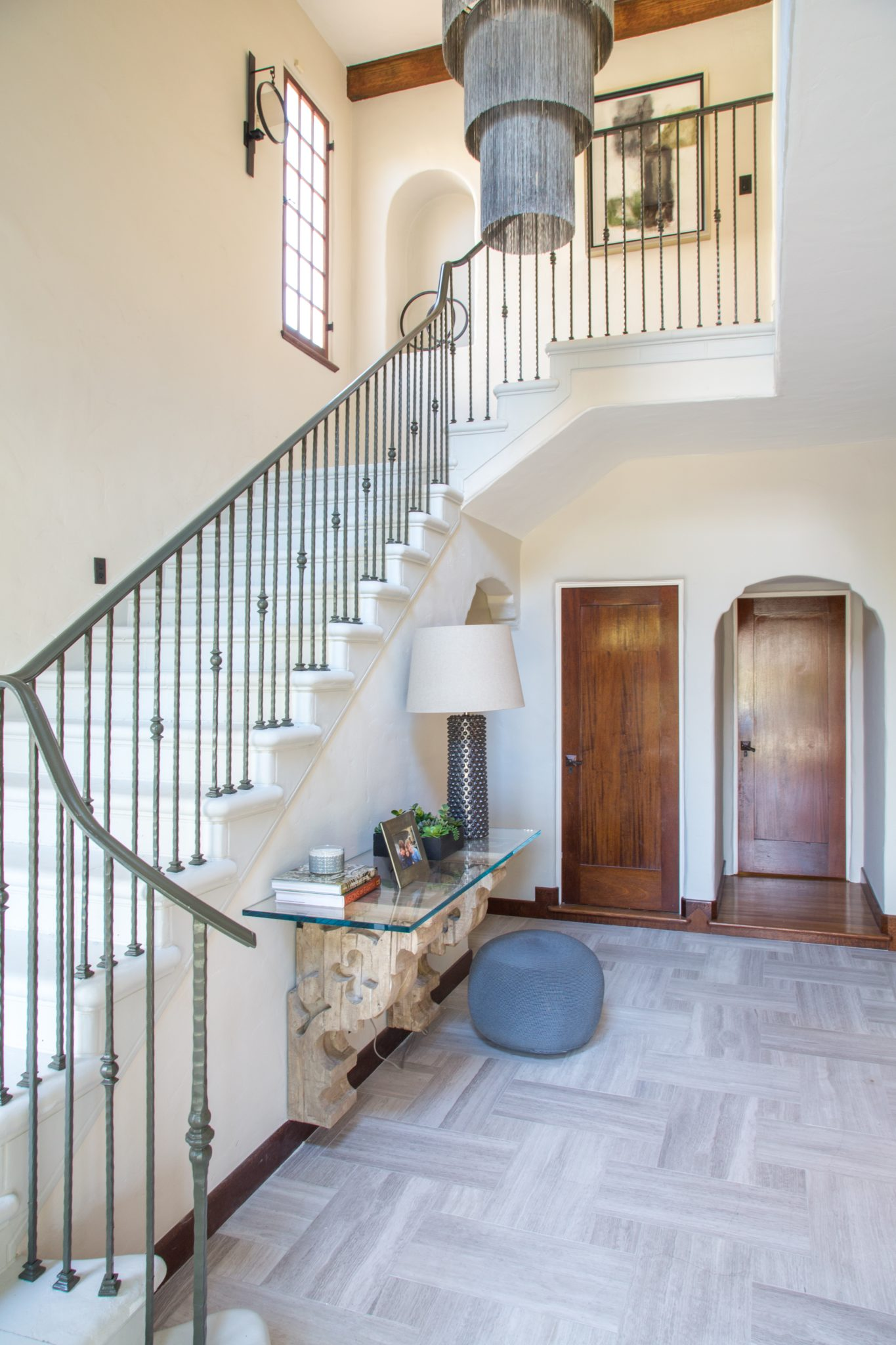 A sophisticated foyer with stone floors and iron railing by dmar Interiors