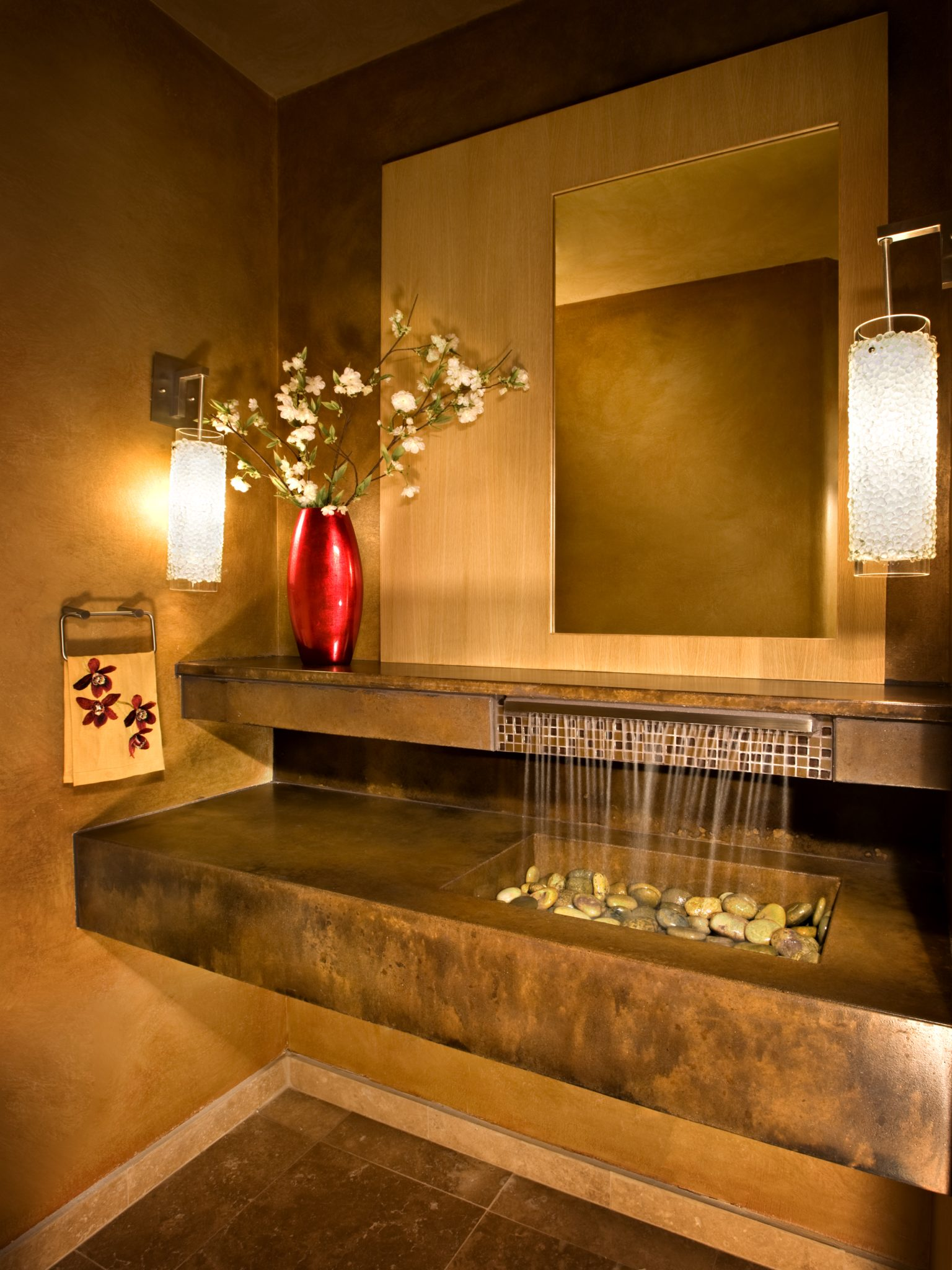 Contemporary zen powder room with custom concrete vanity and a waterfall faucet by Sesshu Design Associates