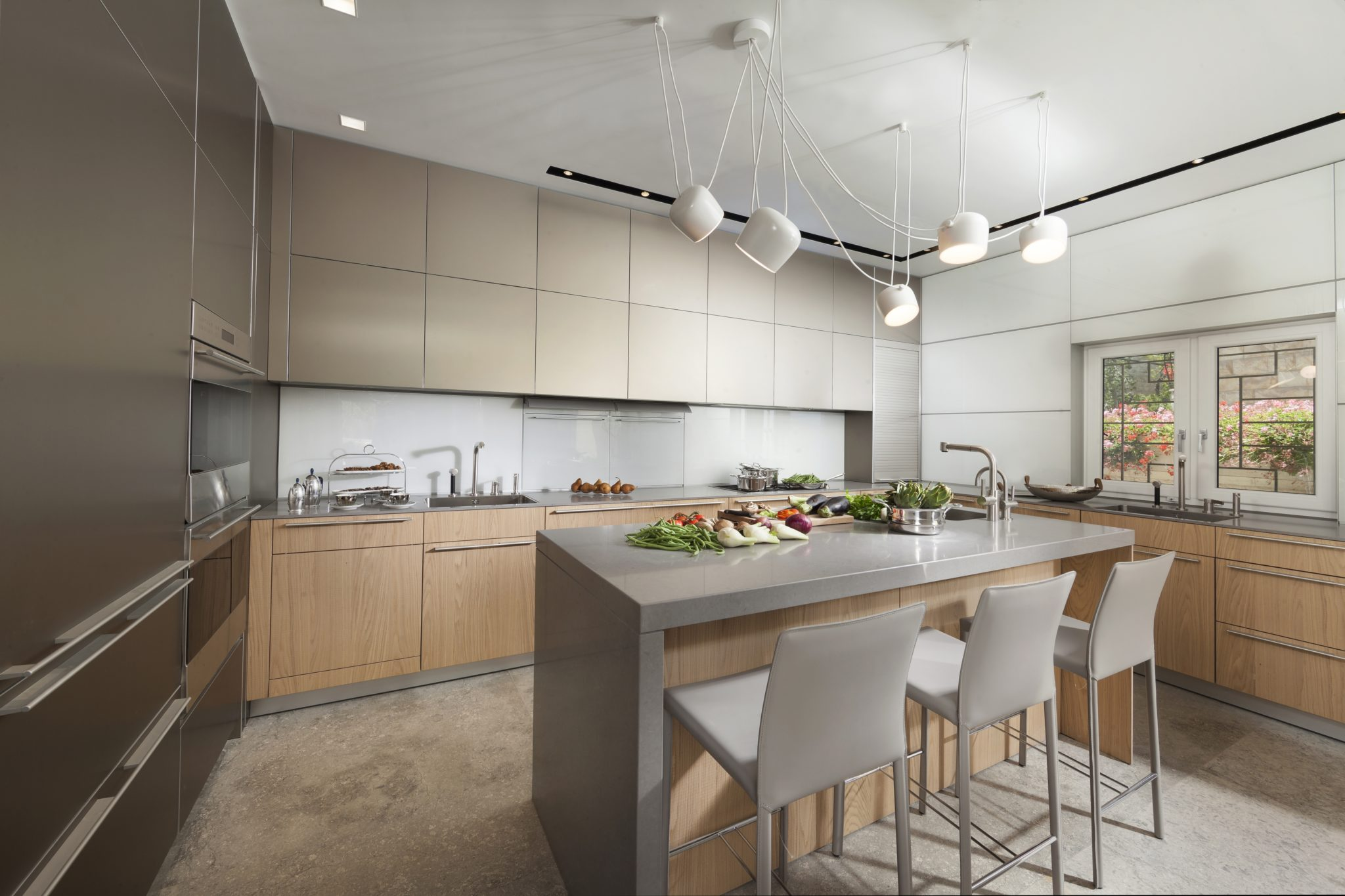 Modern kitchen with wood and grey cabinets, glass backsplash and island. By Annette Frommer Interior Design