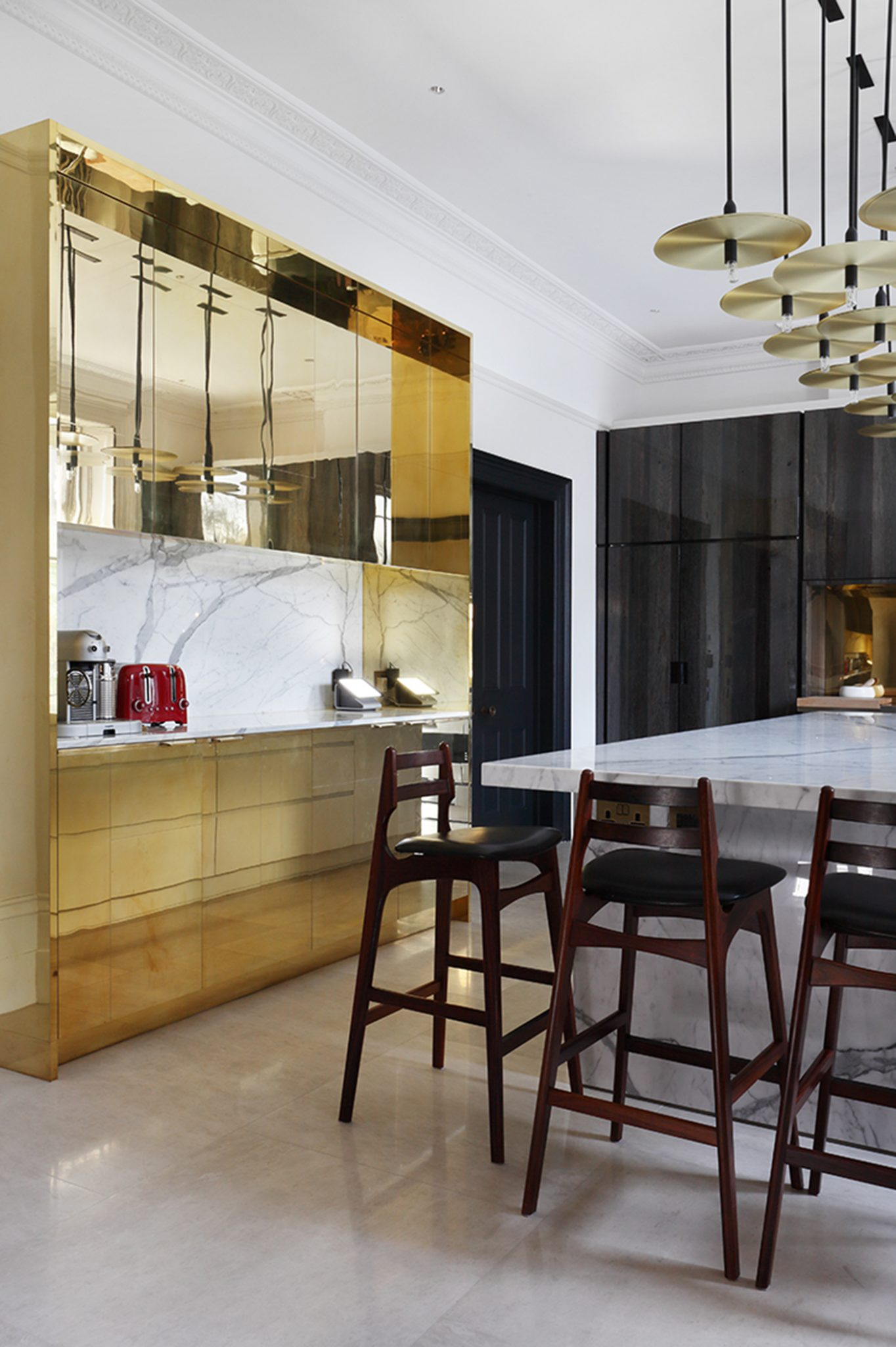 Polished brass creates a dramatic feel in a kitchen area. By Carden Cunietti