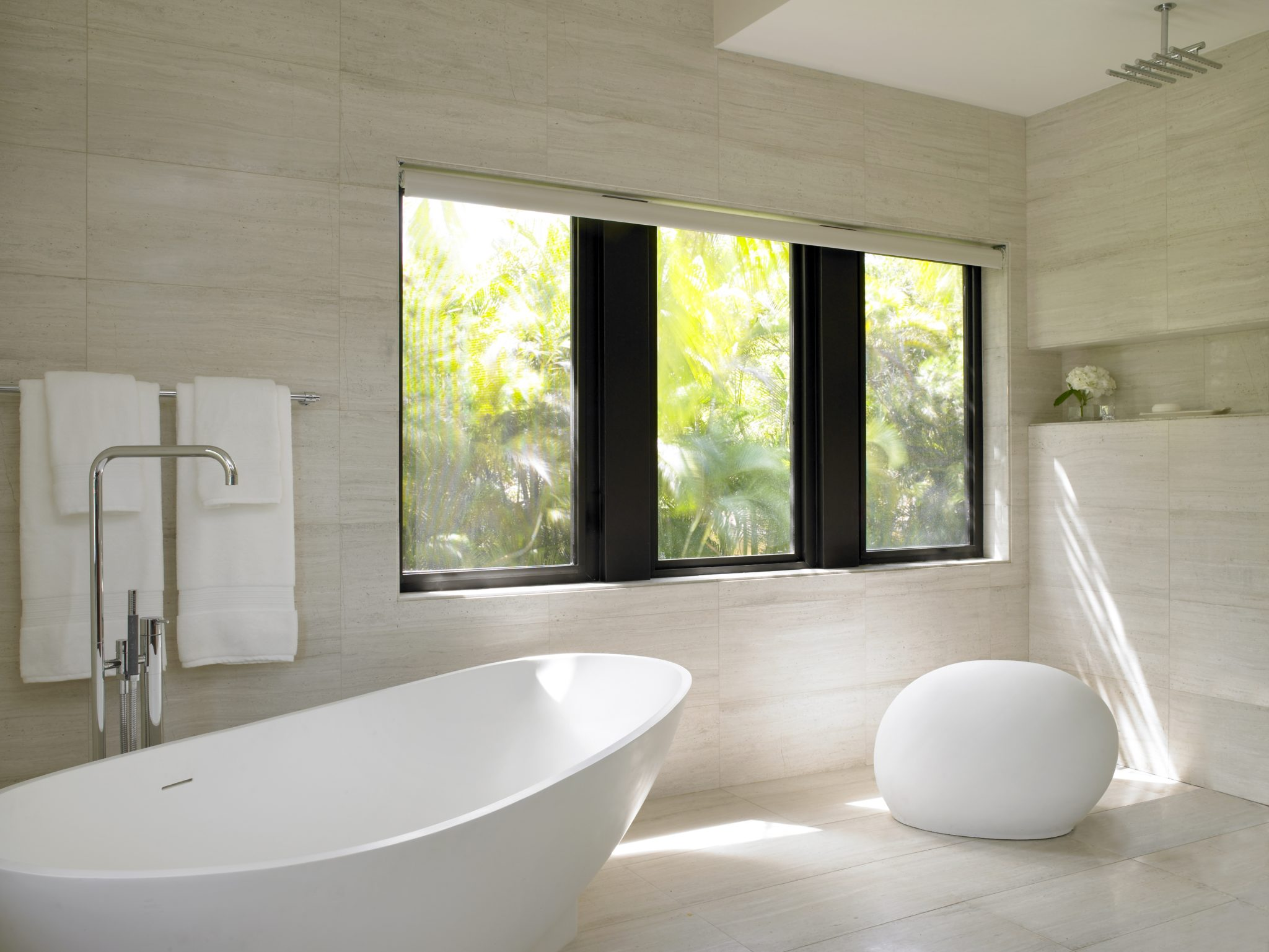 A modern white master bath offers a concrete stool and a freestanding tub and shower that share the sloped floor, so water spills into a slotted drain at wall's edge. By Michael Wolk Design Associates