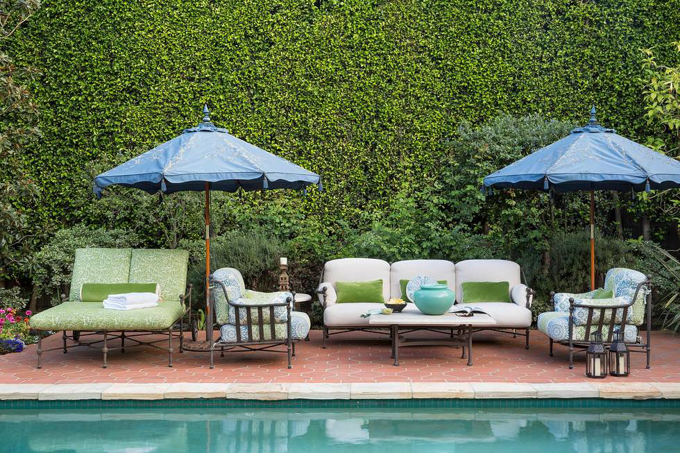 Comfortable, bronze-framed pieces of furniture perch poolside with blue Santa Barbara sun umbrellas, all sitting on a Spanish tiled deck.