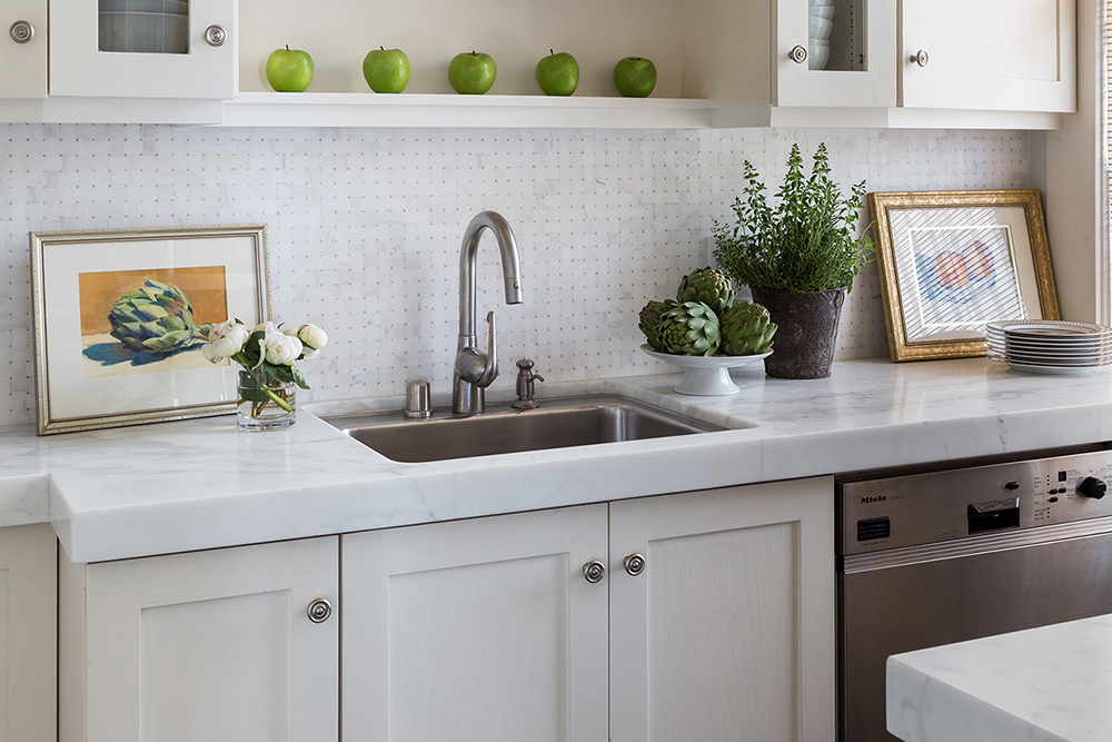 Airy gallery kitchen with Calacatta countertops and mosaic backsplash by Cecilie Starin Design