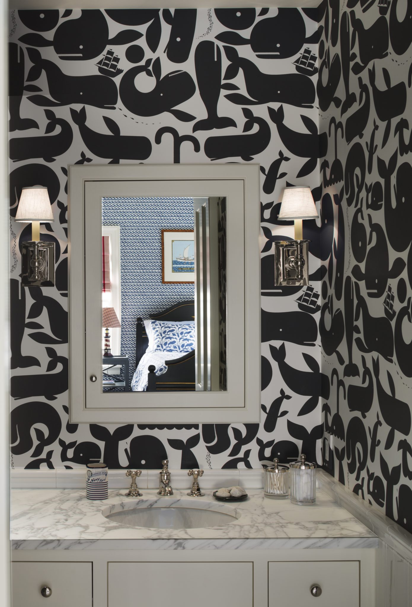Playful bathroom with black and white whale wallcovering and wall sconces by SLC Interiors