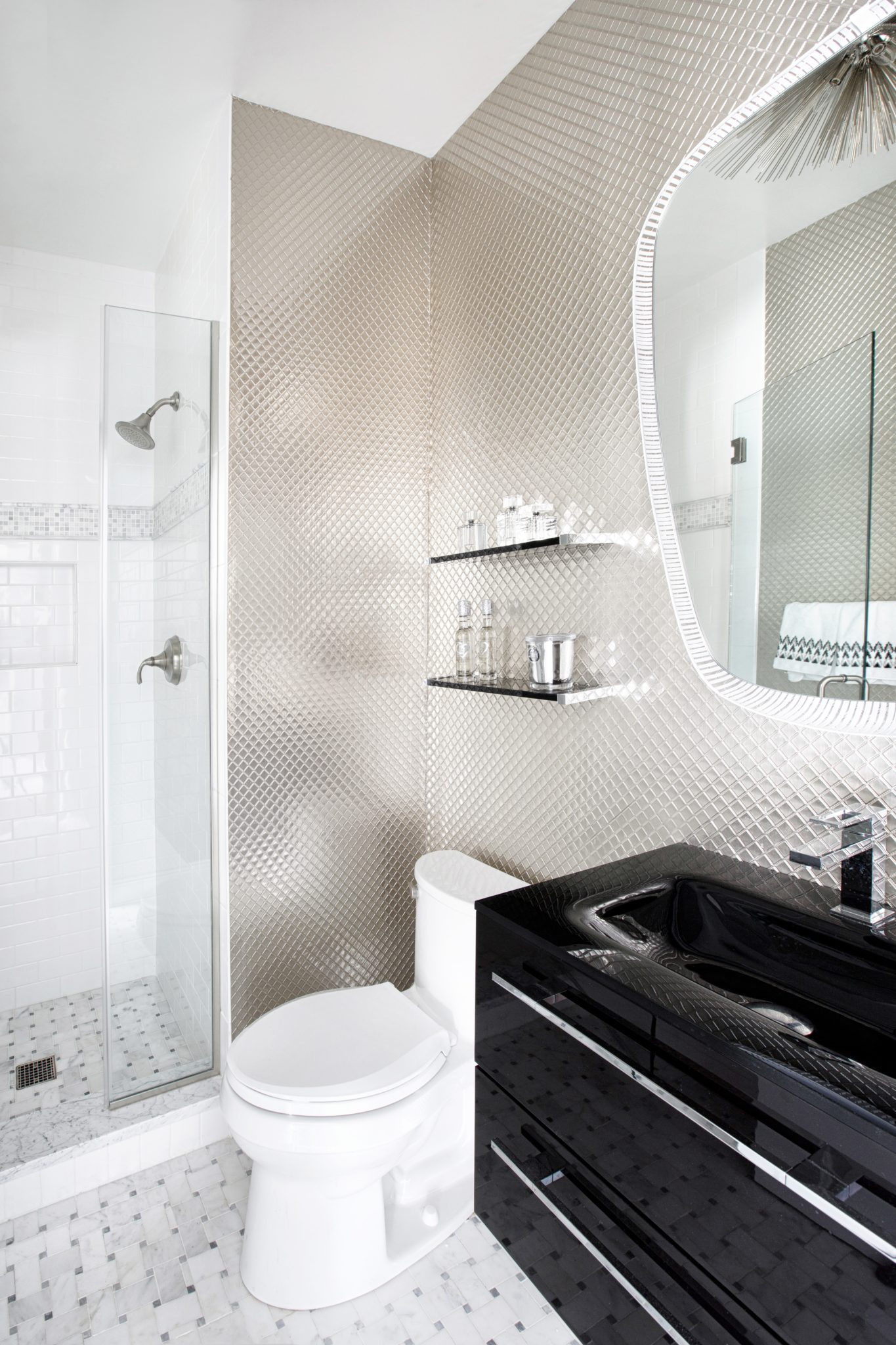 Black bathroom vanity pops against a quilted lacquer wallpaper & back lit mirror by Laura Michaels Design