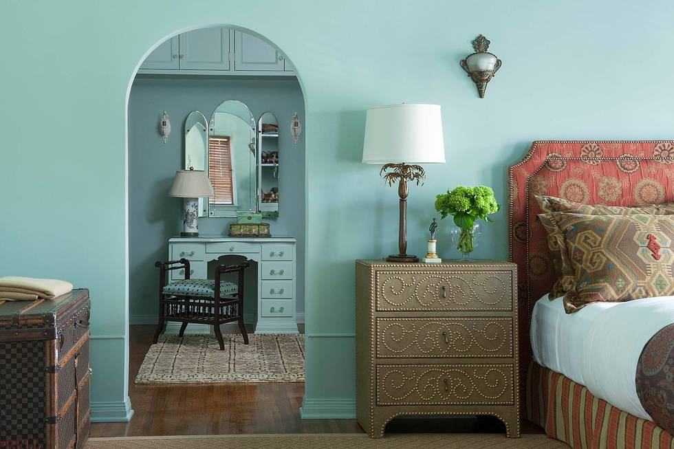 The guest bedroom and dressing room were given a Moroccan flavor with walls painted in Benjamin Moore's Wyeth Blue, nail-studded bedside tables by Horchow, a headboard covered in Hanover, and large bed pillows in Balerno, both by Pindler.