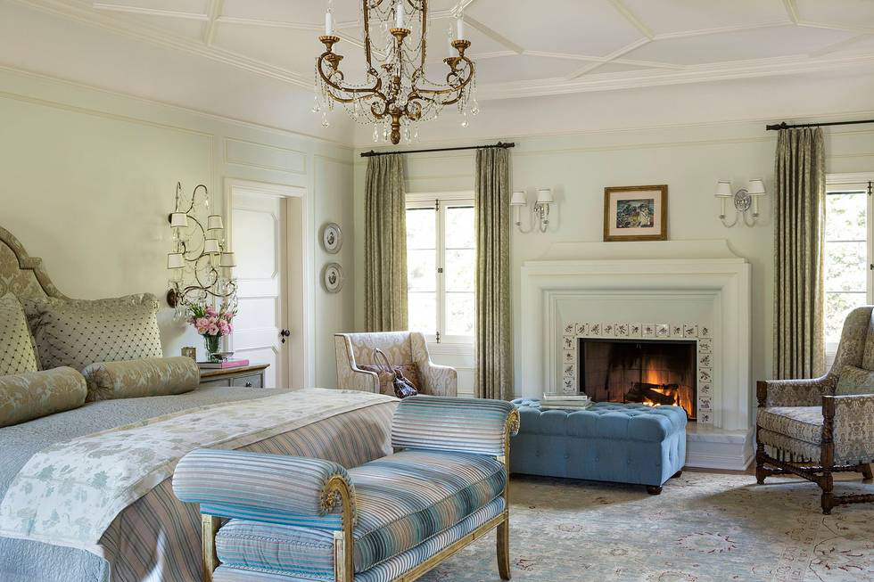The master bedroom is a restful spot painted Hint of Mint by Benjamin Moore. The custom-designed headboard is upholstered in a Cowtan and Tout damask, and the sparkling chandelier and crystal sconces are vintage. Thomas Callaway designed the roll armed bench at the foot of the bed. The frame is gold leafed and upholstered in Sheila Coomes' Nomad velvet.