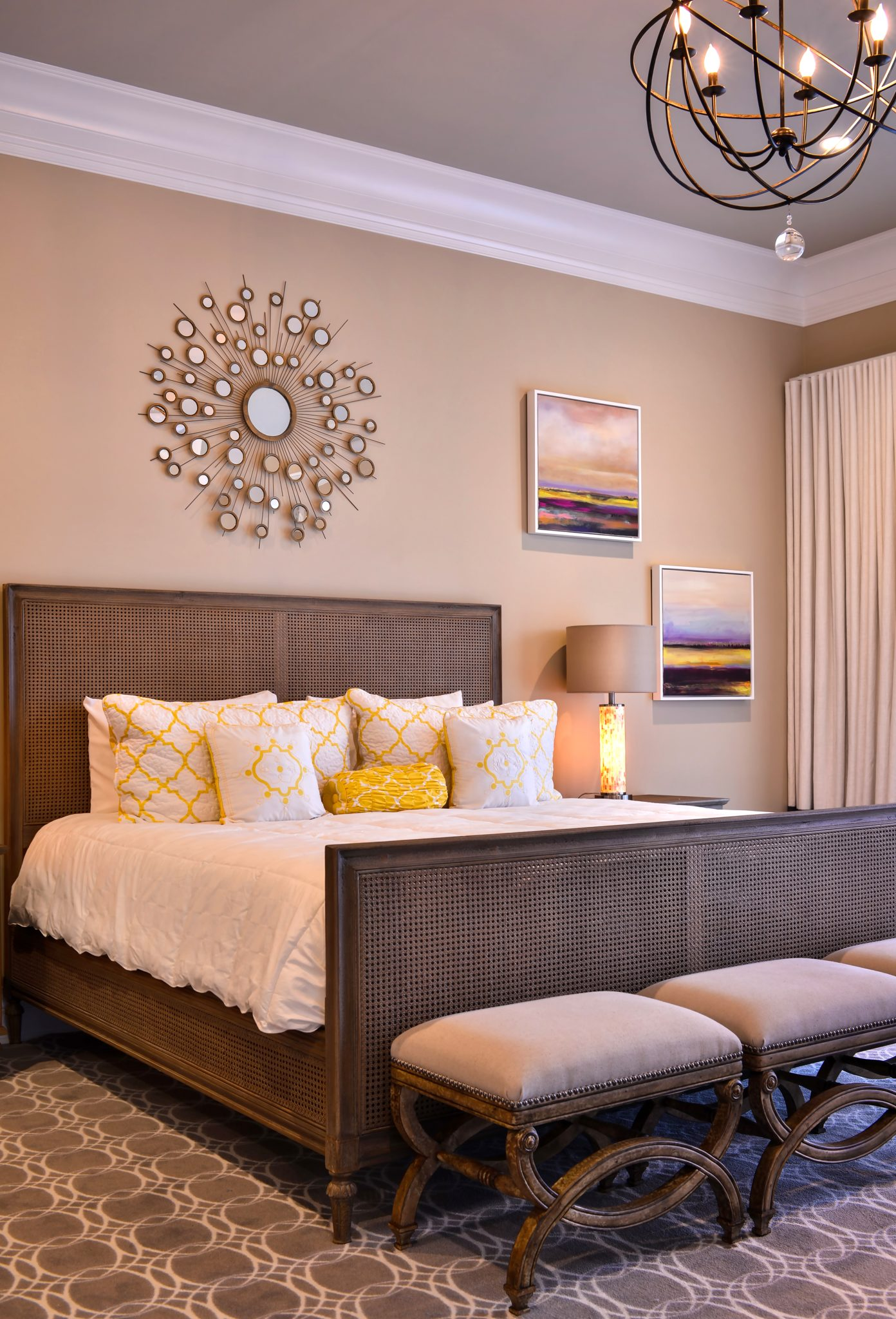 Guest bedroom with large chandelier rug wall art yellow pillows by Keith Mazzei Interiors
