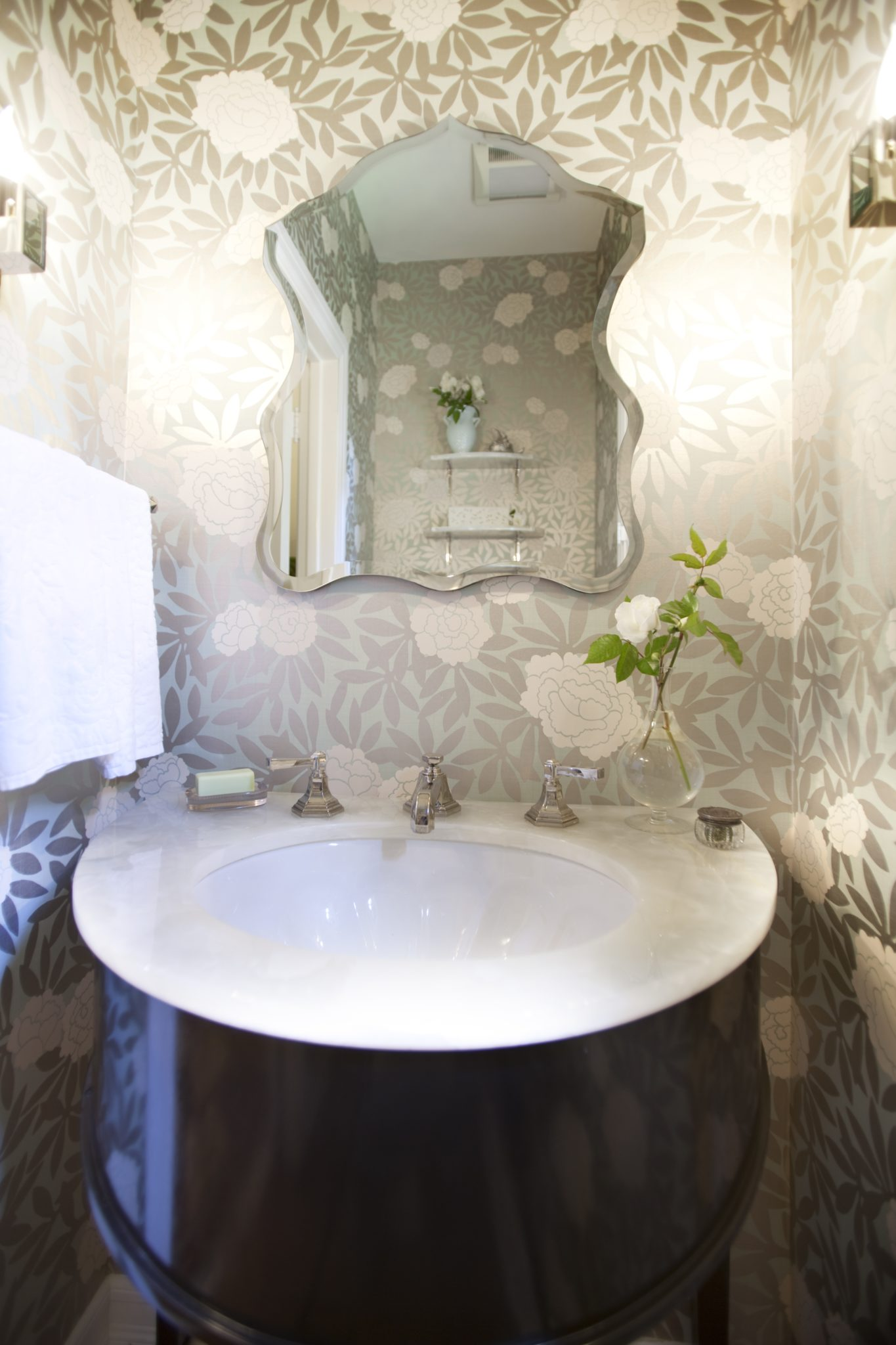A locally made bespoke vanity, marble countertop and rose patterned wallpaper. by Sarah Barnard Design