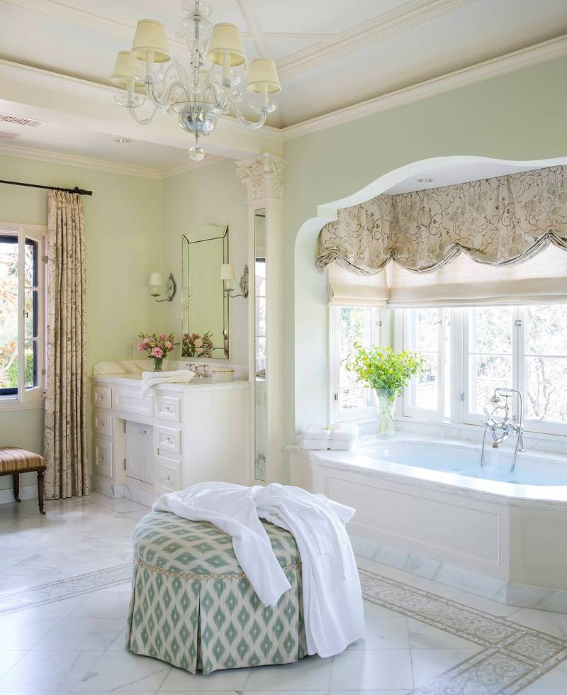 The master bath has a spa-like serenity, featuring a water tonality on the walls, white marble flooring with mosaic borders, a crystal chandelier, and Venetian mirrors. It is spare but light filled, giving it a clean, relaxing freshness.