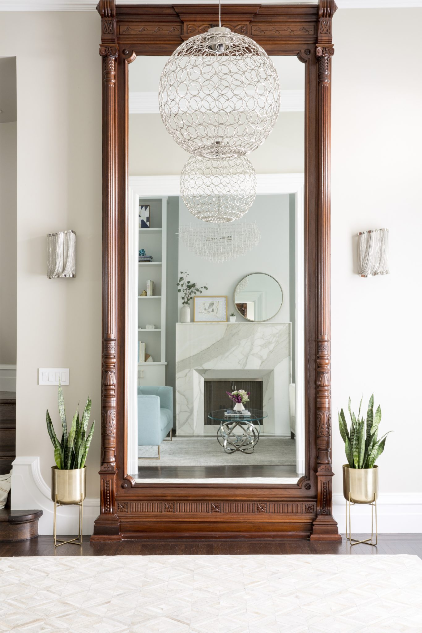 Rich Wood Entry with Grand Staircase and Floor to Ceiling Mirror by Coddington Design
