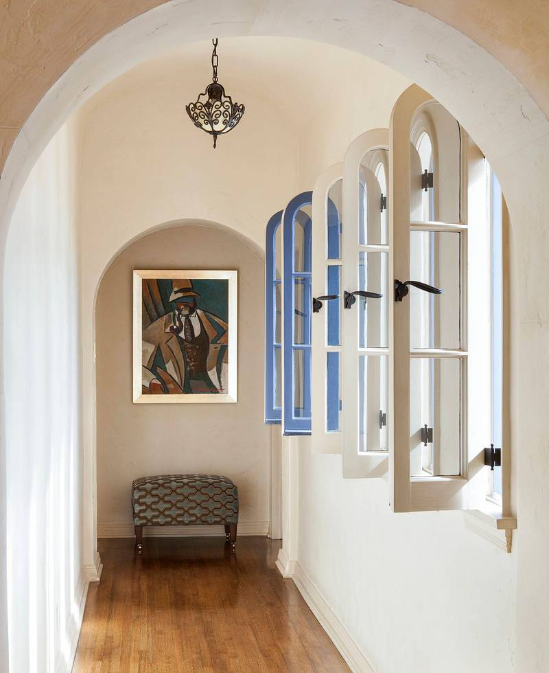 Through arched doorways, a second floor hall is punctuated with a line of open window sashes.All photography by Lisa Romerein/OTTO.