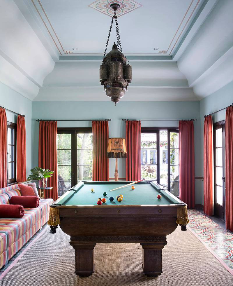 The robust but graceful plaster work of the billiard room came to life when painting it a custom blue-green, accented with stenciled borders, a rosette, and contrasting curtain columns of Kravet red linen. A room-length banquette in Quadrille's Cadet Stripe fabric with red bolsters and a large Moroccan lantern fixture contribute to the riad flavor of the space.