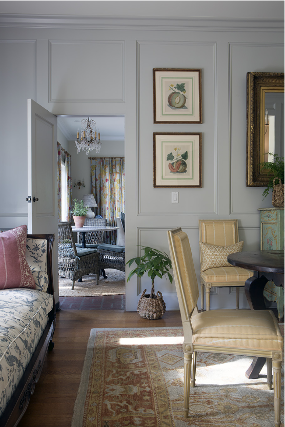 """""""I love these rooms because they are somewhere between formal and casual, which is where I love our work to be. It is an elegant, layered interior, but nothing is too precious to be used. This family has three kids and three dogs, and they truly live in all the rooms. The palette was established by the antique painted chest in the dining room, and is subtly repeated in the Raoul textile drapery on the far wall of the family room. I love mixing wicker with an antique French chandelier, antique Oushak rugs with baskets and antique French chairs upholstered in a gorgeous Soane textile. We added the paneling to the dining room which was the first layer and adds so much architecture to the room."""" —Elizabeth Vallino, Elizabeth Vallino Interiors"""