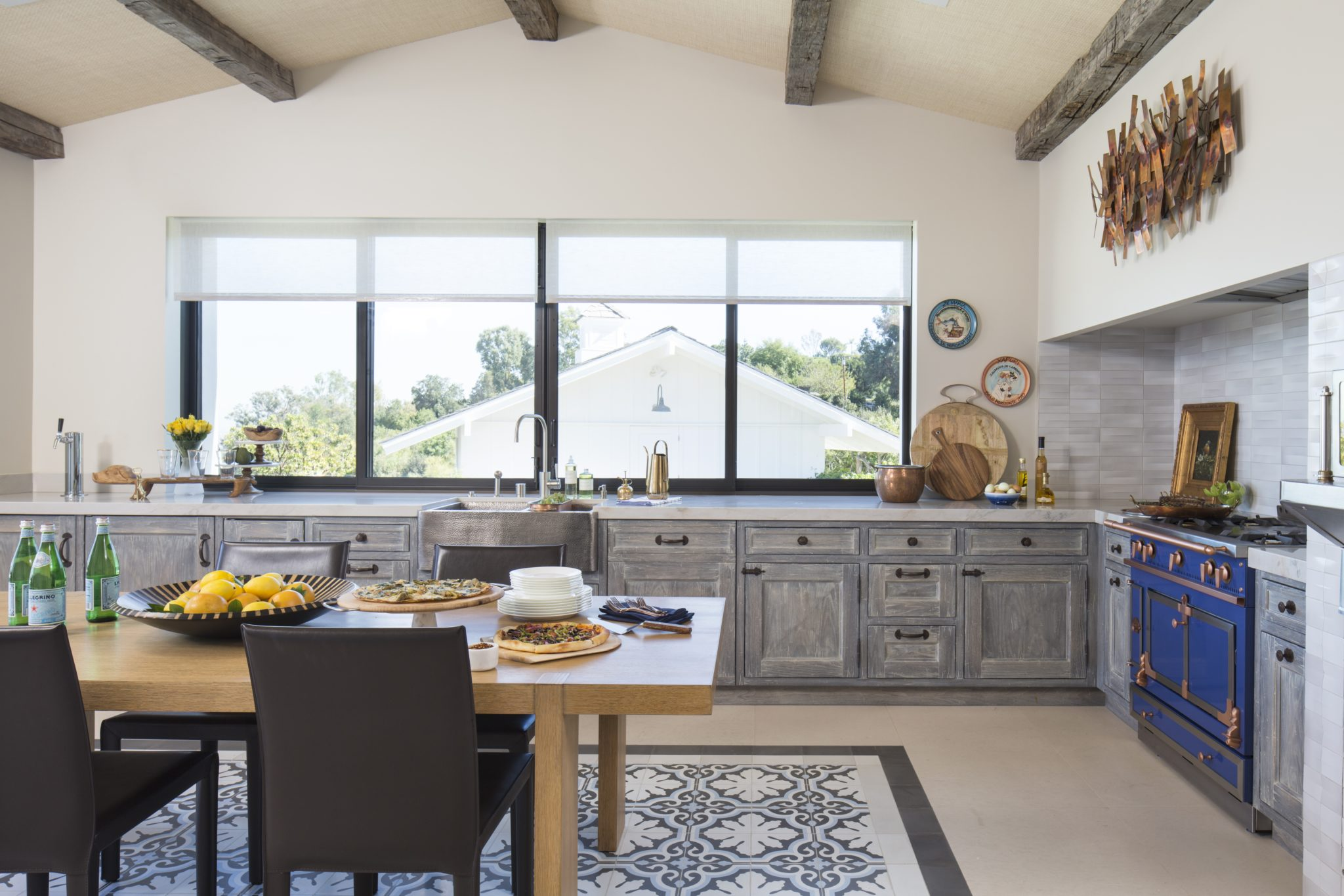 Indoor outdoor kitchen, exposed beams with blue La Cornue and inset tile floor. By Cooper Pacific Kitchens