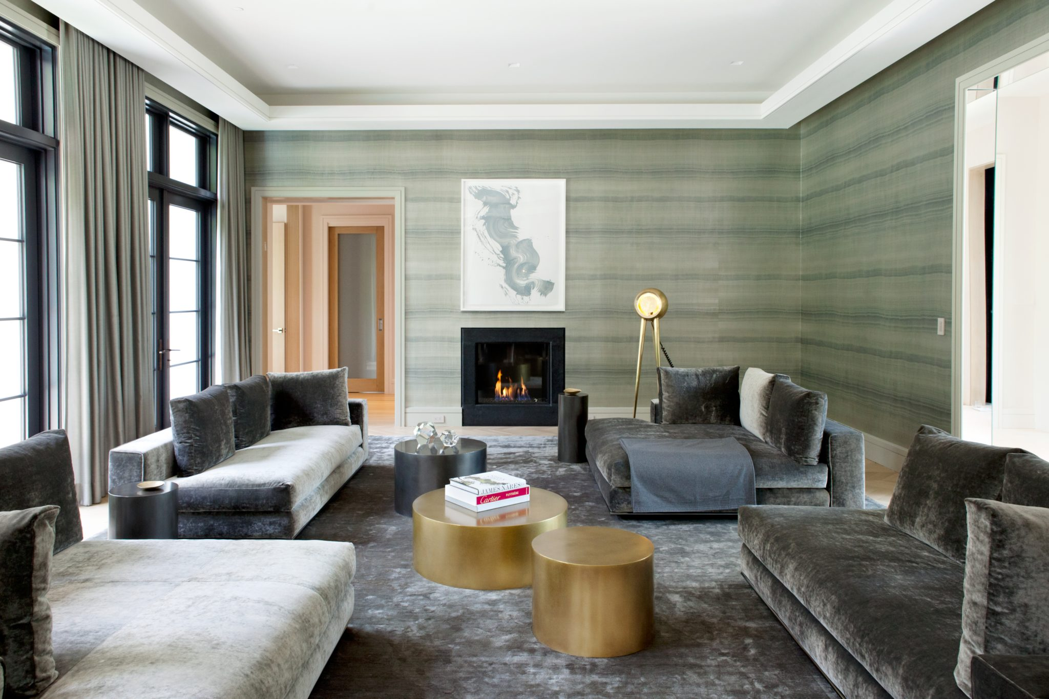 """""""The living room shot from my Tenafly project best representsmy style because it is both soothing and intriguing. The coloring of the room is very unique. It's a green/grey which is rarely seen.The Armani/Casawallpaper gives the illusion of being inside a clam shell. The seating layout is very dynamic, as I took Minotti sectional sofas and separated them to create flow throughout the room. The 'mushroom city' tables in brass and blackened bronze are all different heights and diameters. The finishing touch is the standing lamp from Material Lust [Orphan Workreissues designs from the company's archives]. I always like to add something unusual in a space, that makes you look twice.""""  —Jessica Gersten,Jessica Gersten Interiors"""