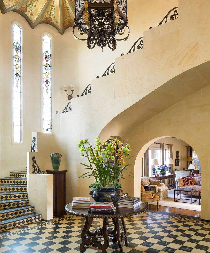 The scored plastered walls of the expansive foyer were faux painted to appear as golden limestone blocks, with the existing checkered marble flooring and vertical stained glass windows leading up the staircase toward a gold leafed and stenciled ceiling, which was repaired back to its original splendor.