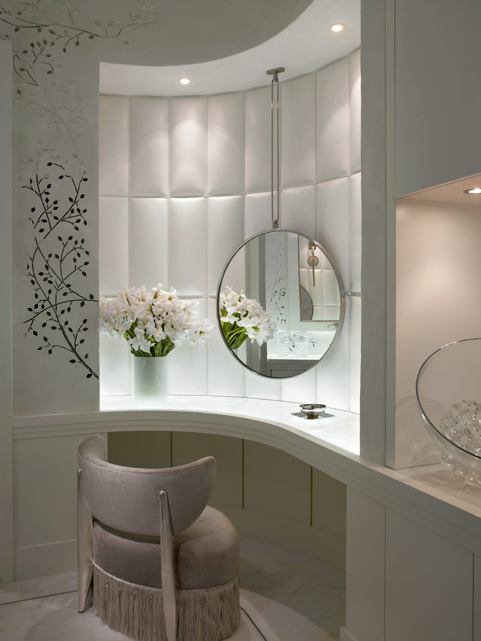 A neutral vanity is dramatized by a French mirror on custom leather panels. by Alene Workman Interior Design