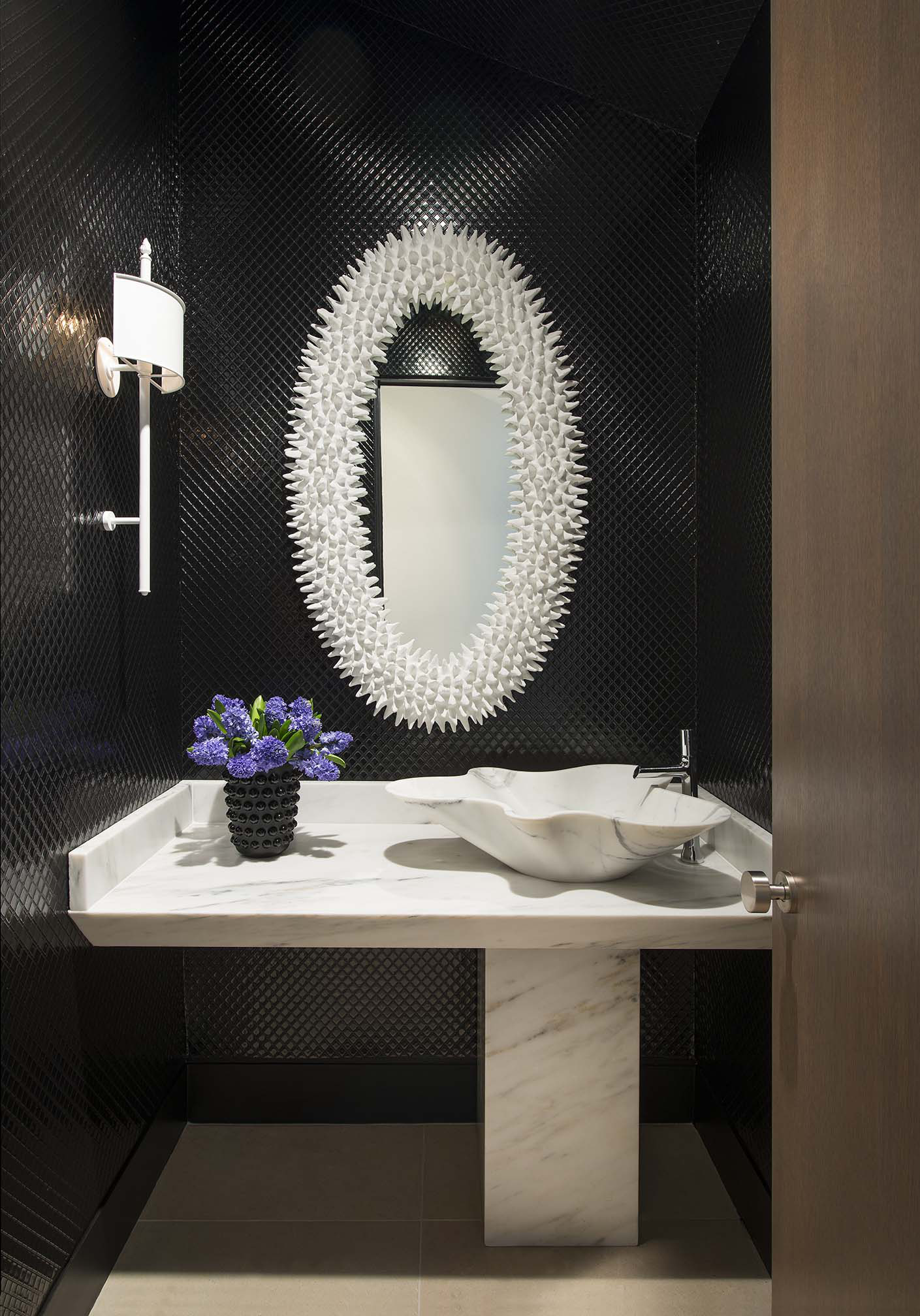 Sleek powder bath with custom marble vanity and sink by Denise McGaha Interiors