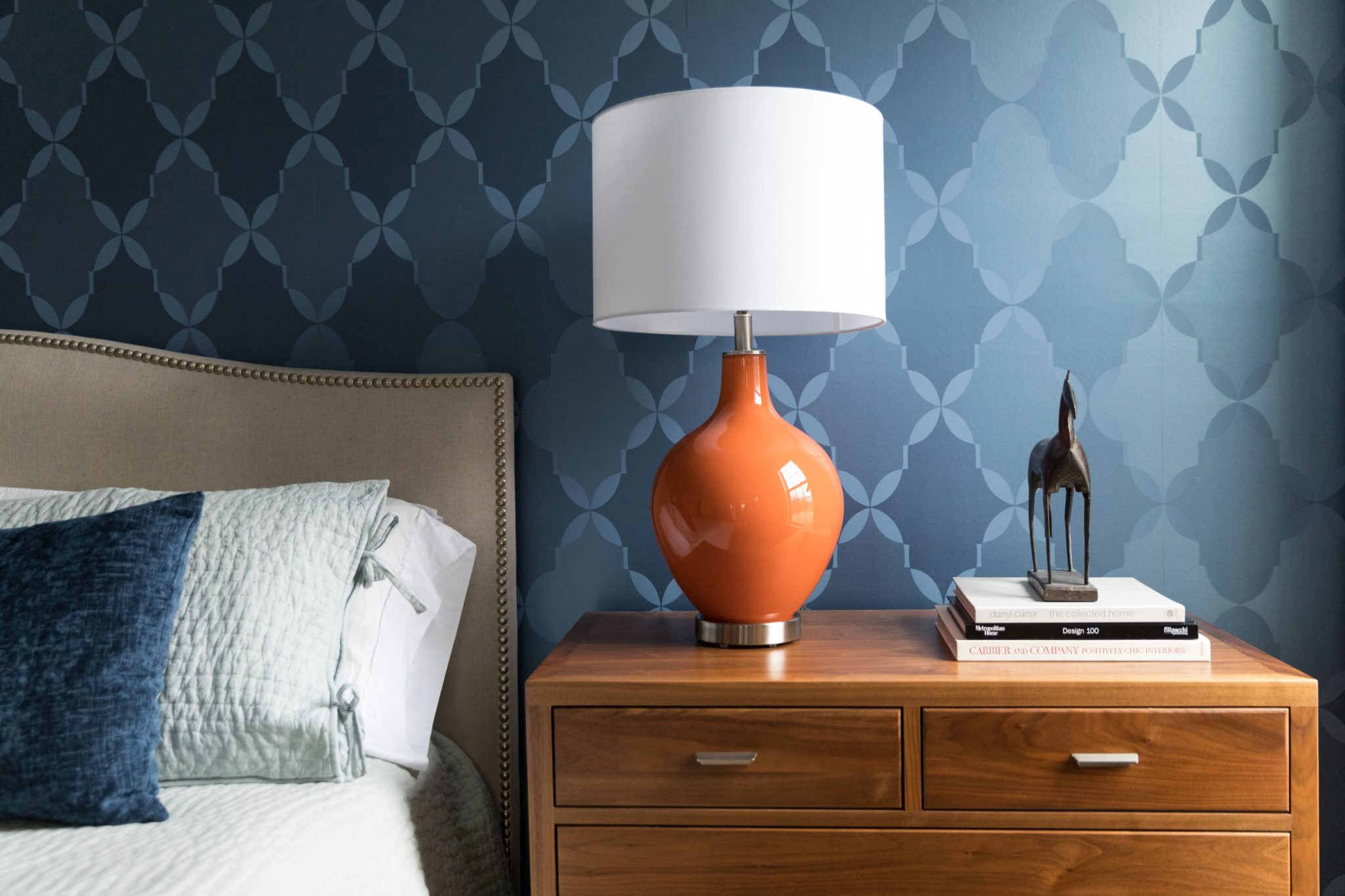 Opposite colors contrast in a modern bedroom with a trellis wallpaper. by Laura Hodges Studio