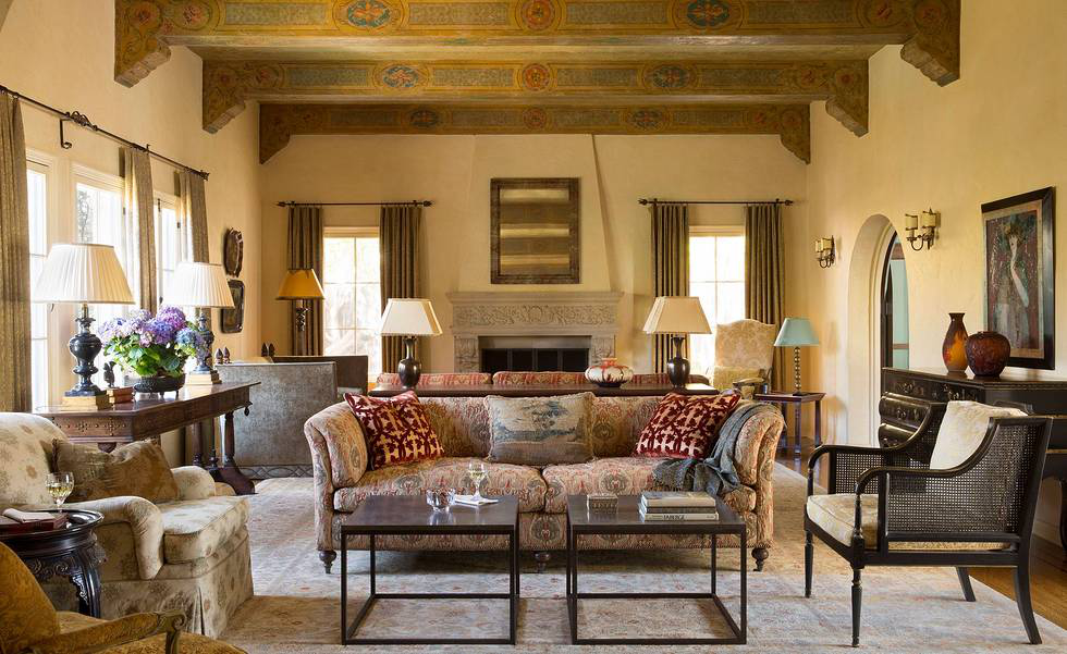 """The living room is divided into two seating groups of custom furniture including back-to-back sofas. With glazed walls in a buttery tone, rich fabrics were chosen to resemble remnants of Old World textiles. The front sofa is upholstered in Kravet's Bolgheri with the red square pillows in """"Folk Manor House"""" by Scalamandre and an antiqued pillow by Y & B Bolour. The stenciled beams and corbels are original to the house."""