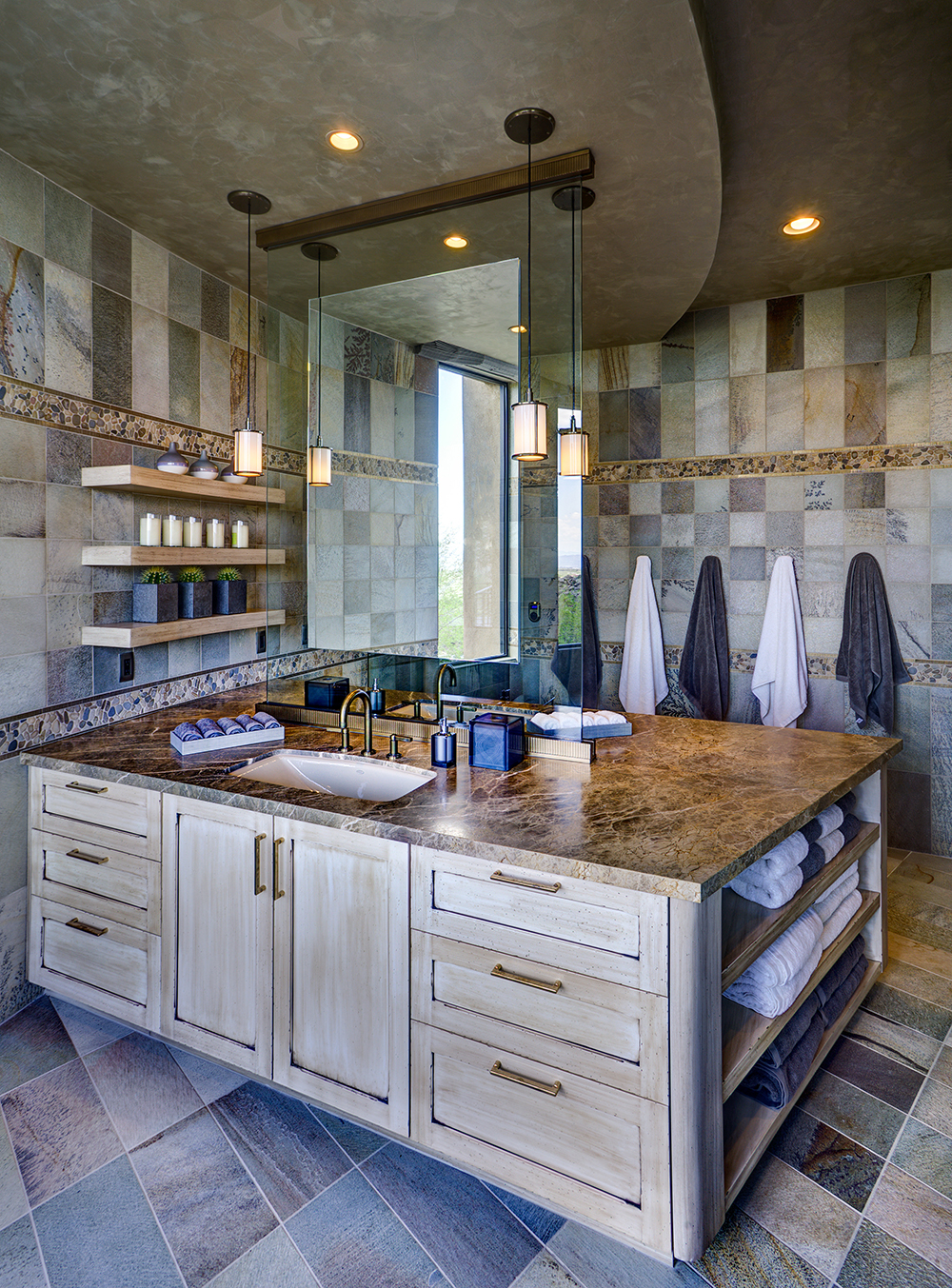 Installing back to back vanities with a suspended mirror partition sets the master bath apart. by Lori Carroll & Associates