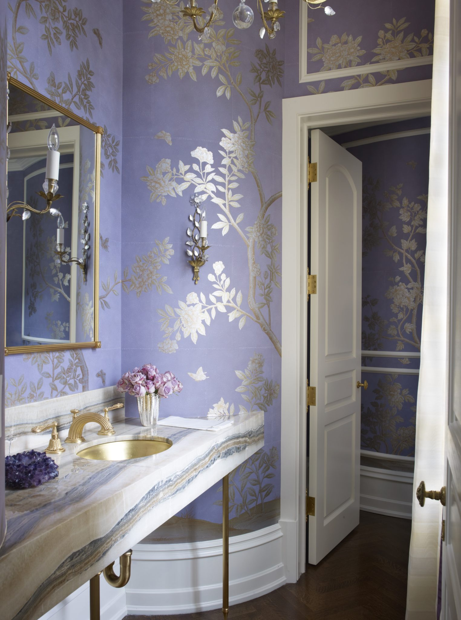 Chic powder room with colorful marble vanity and purple wallpaper by Suzanne Kasler Interiors
