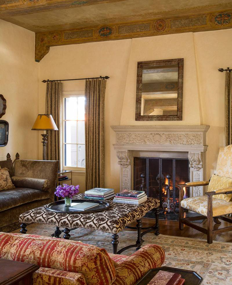 A second seating group near the living room fireplace is composed of two sofas, a large turn-legged ottoman, and a high-backed armchair. The rolled arm sofa is upholstered in Villa Venezia's Saffron Novelty, and the Knoll-style sofa is covered in Zoffany, Chelsea Quays, Olive. Both pieces were designed by Thomas Callaway Bench Works. The ottoman is upholstered in Schumacher's Lorenzo silk velvet.