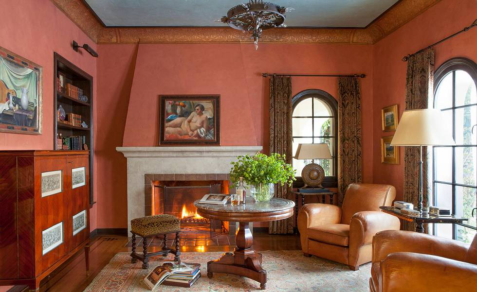 The study is situated off the foyer, opposite the living room. It is painted a custom Pompeian Red with the ceiling painted a contrasting pale blue, embellished with a gilded stencil of Callaway design on the coved border. The French bar cabinet and the leather club chairs are vintage, and the paintings throughout are from the owner's collection.
