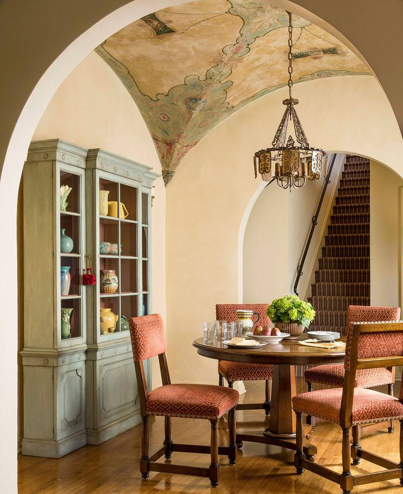 Beneath a stenciled groin arched ceiling, the breakfast room holds a custom walnut table and a set of chairs in a Schumacher fabric. The small breakfront, once mahogany from the 1920's, has been painted a blue-green hue to set off the California pottery inside.