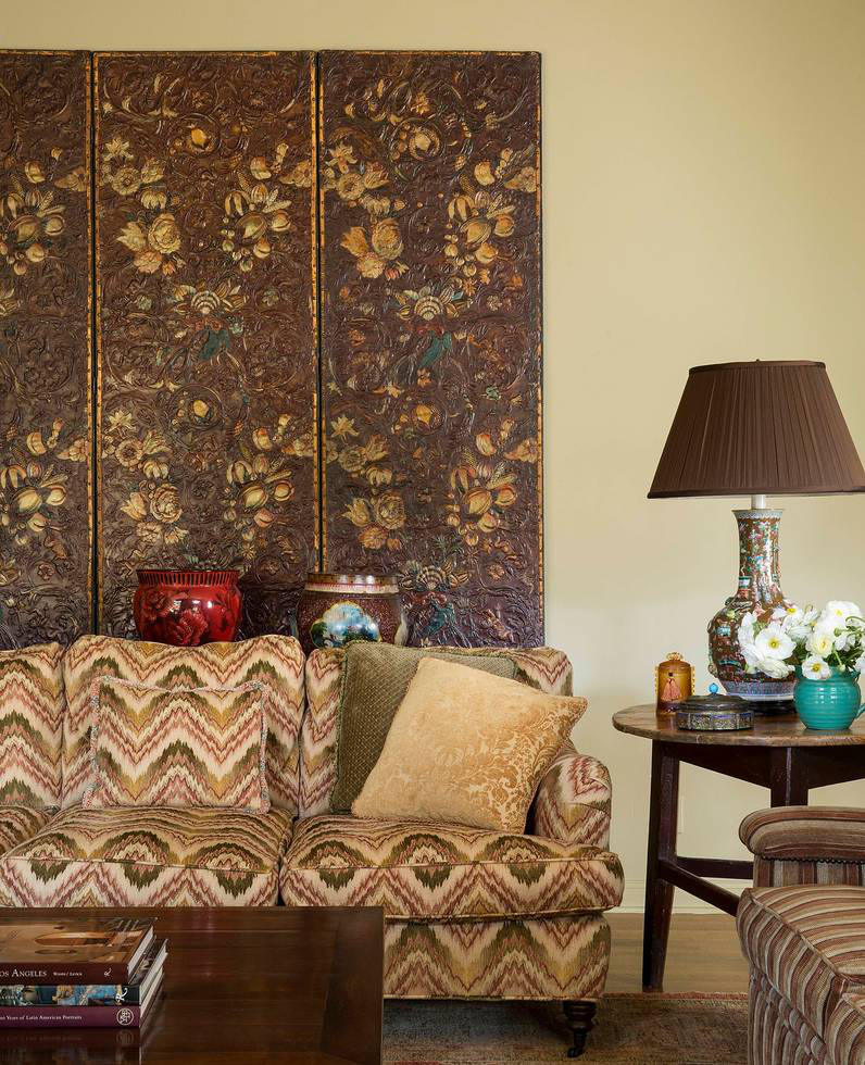 In the family room, a stamped and gilded leather folding screen keeps focus behind a custom Thomas Callaway Bench Works sofa in a flame stitch textile.