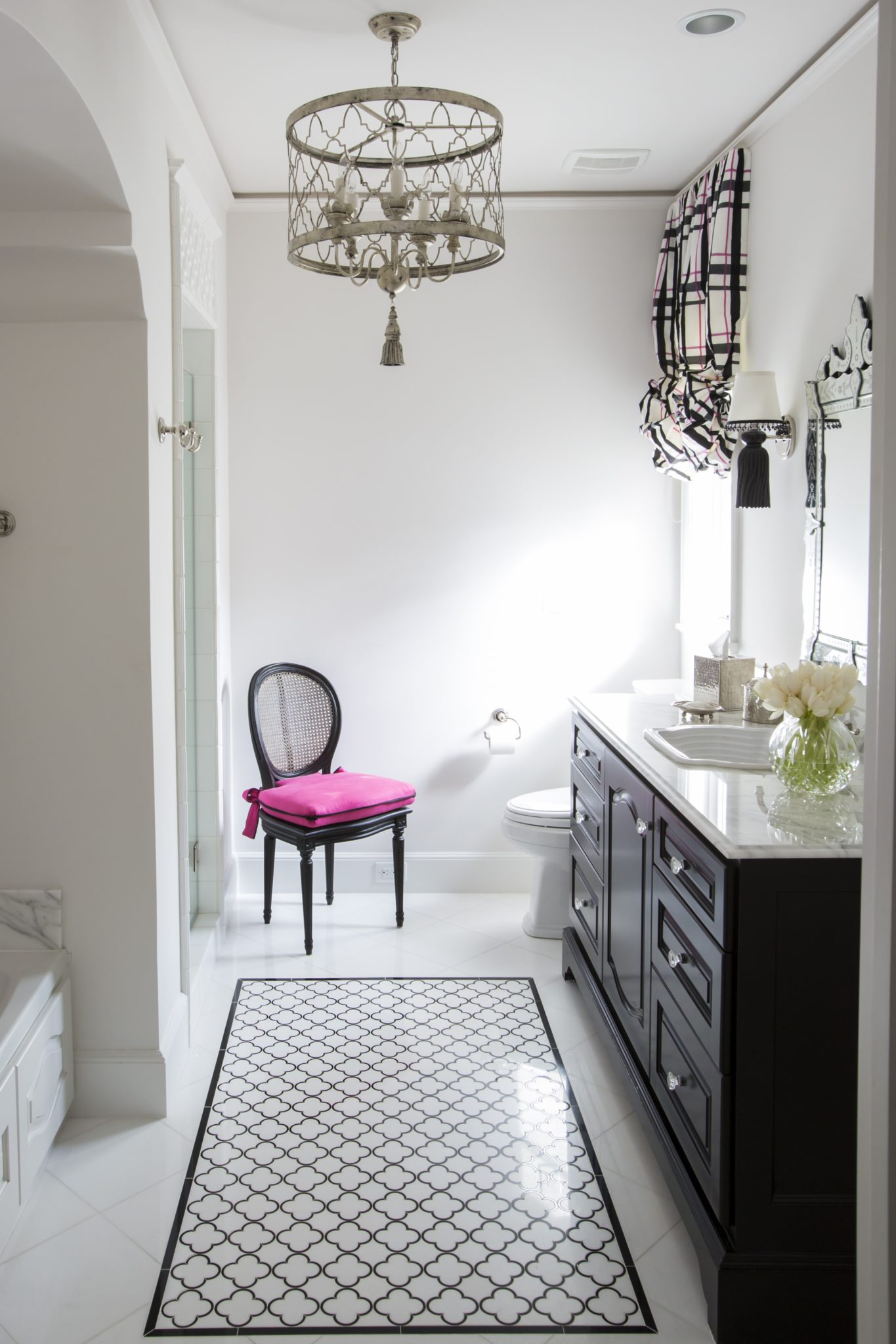 Black andwhite girl's bath featuring decorative tiling, custom colored sconces and a pop of pink by Triangle Interiors