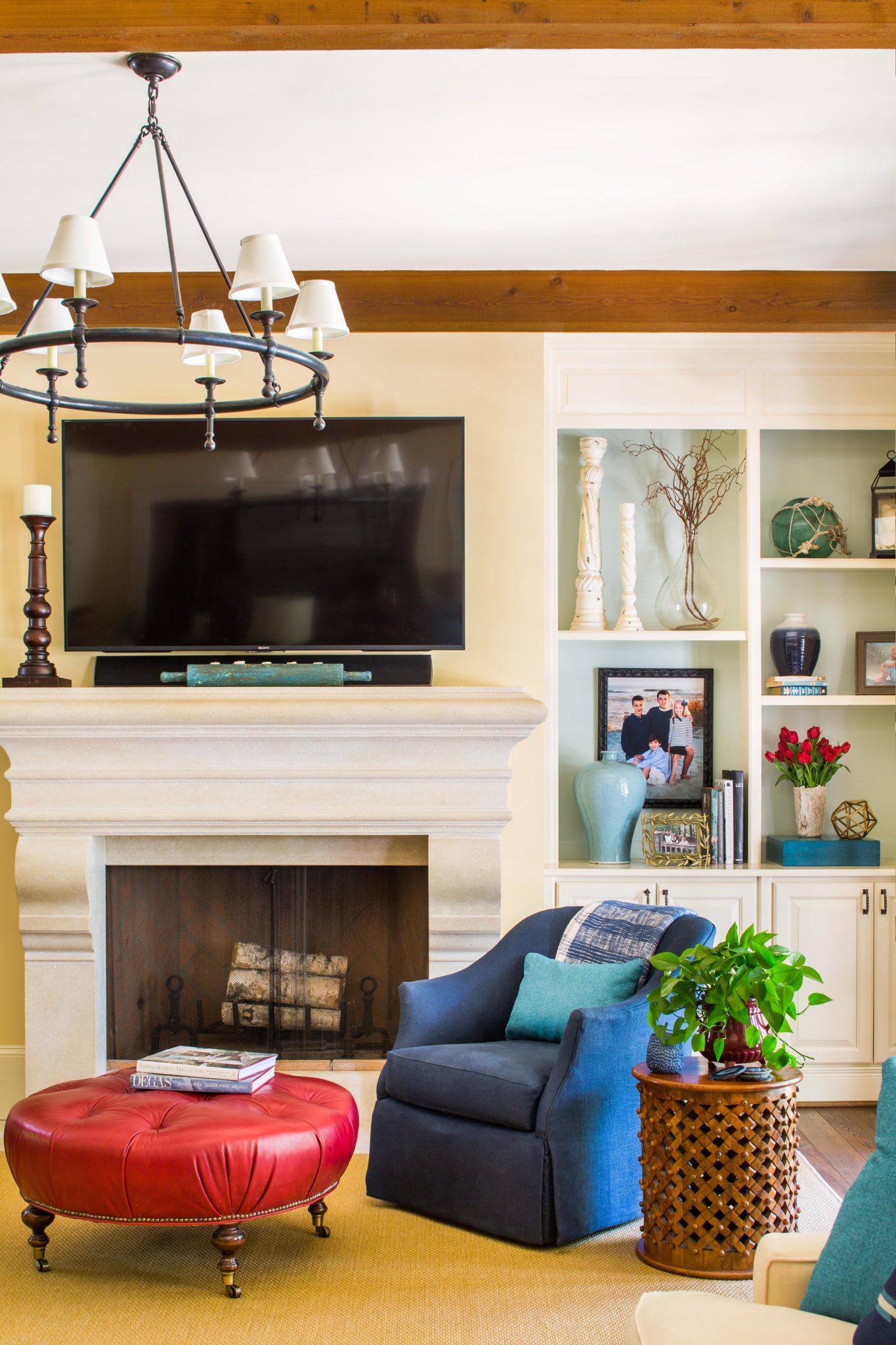 Stone fireplace mantel with bookcases, a swivel chair and red leather ottoman by Meriwether Design Group