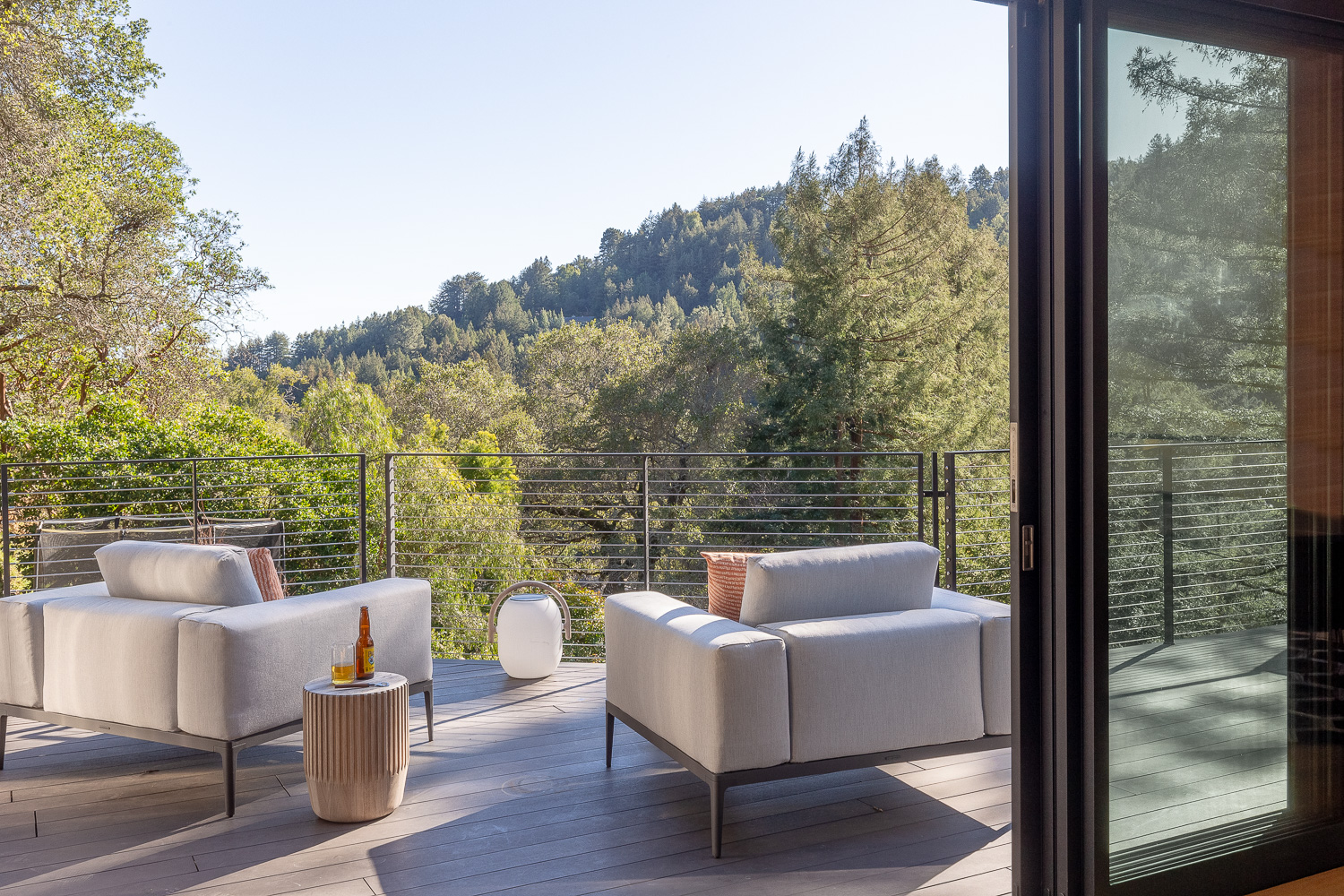 Two plush side chairs and a table from Gloster look out over the beauty of the redwoods. Parlette redesigned the porches with a variety of new elements, including steel cable railings that don't interfere with the views.