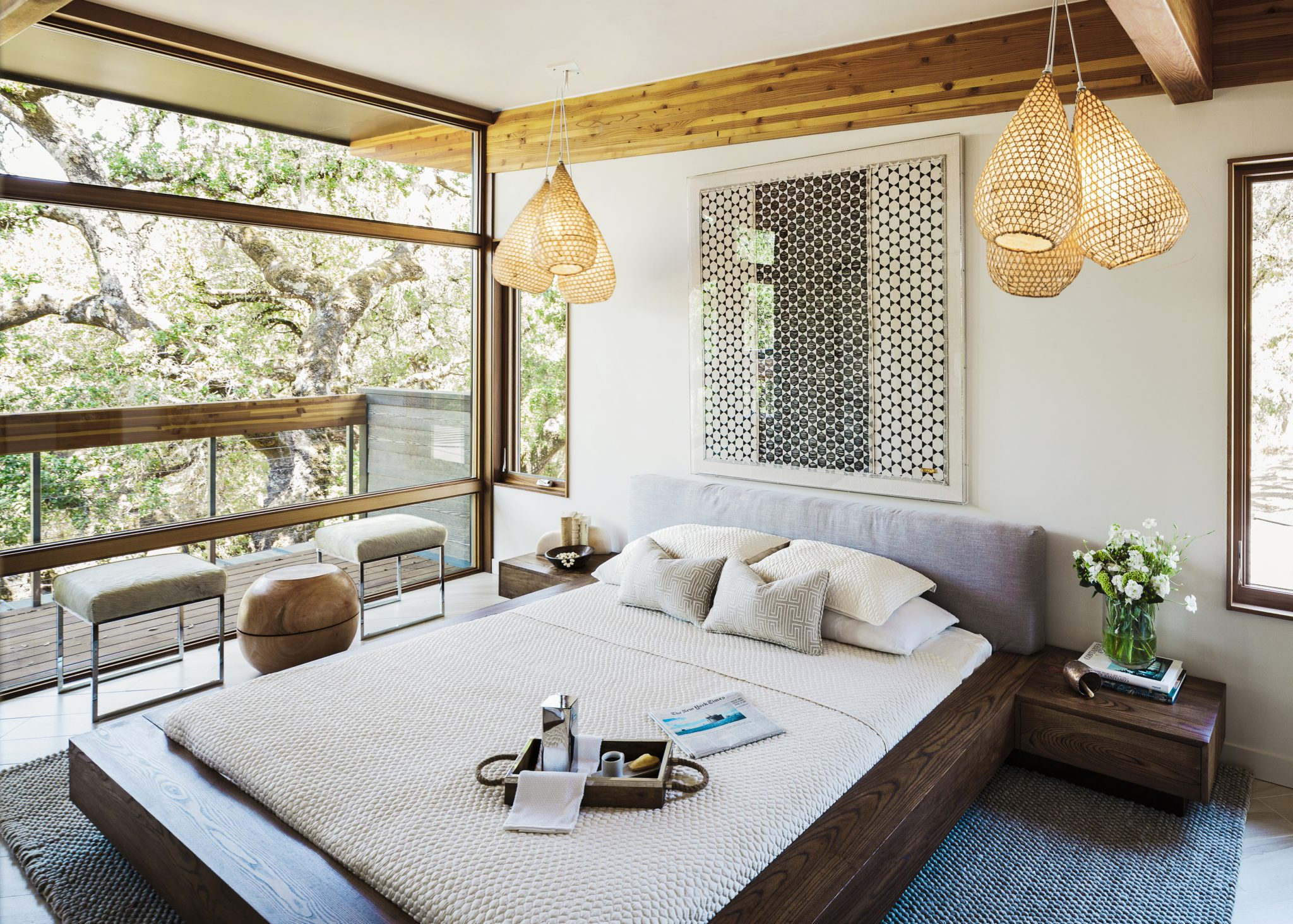 The pendant lighting here was crafted from fishing nets lined with paper, and sourced from Dering Hall. Hammers andHeels crafted the custom,Japananese-style platform bed, which also features a linen headboard,from sustainably harvested poplar wood. The bed is set on a Starkrug, and the cowhide and metal benches and stools are from Scenario Home, with a stool from Bellacor placed between them. The artwork in a lucite frame, calledBiddew Noir,was designed by a Senegalese artist namedJohanna Bramble and purchased from St. Frank.