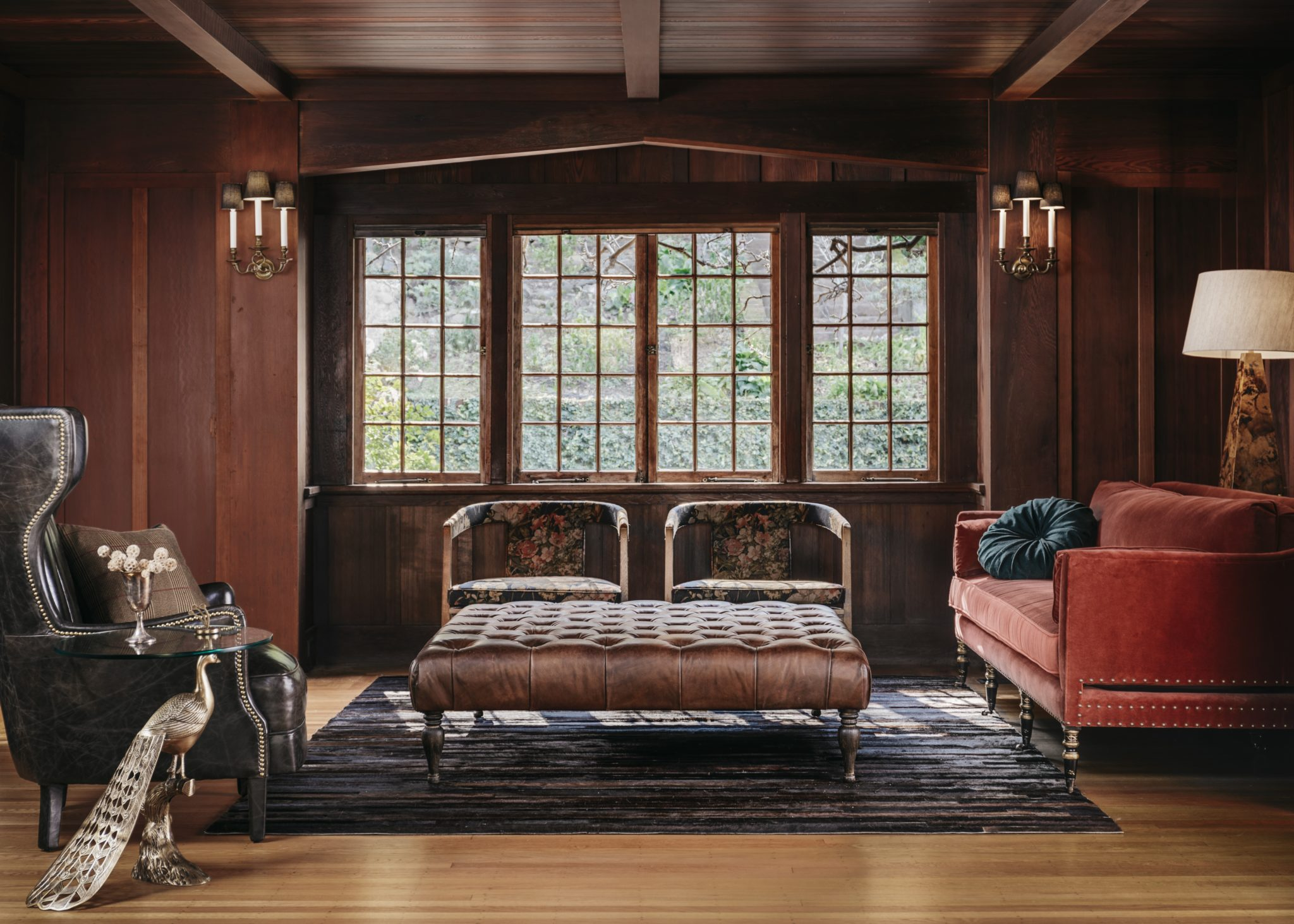 Inspired by classicEuropean designs, the library features wood paneling and sophisticated furnishings, including a regency-style sofa from Coup D'Etat, upholstered in rust orange fabric from Pindler.