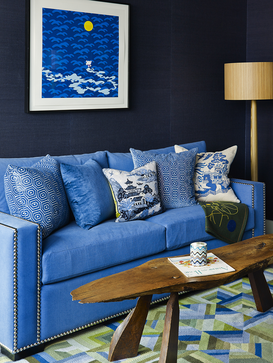 A blue sofa bed sits on a custom colorful patterned needlepoint rug. By Scott Sanders
