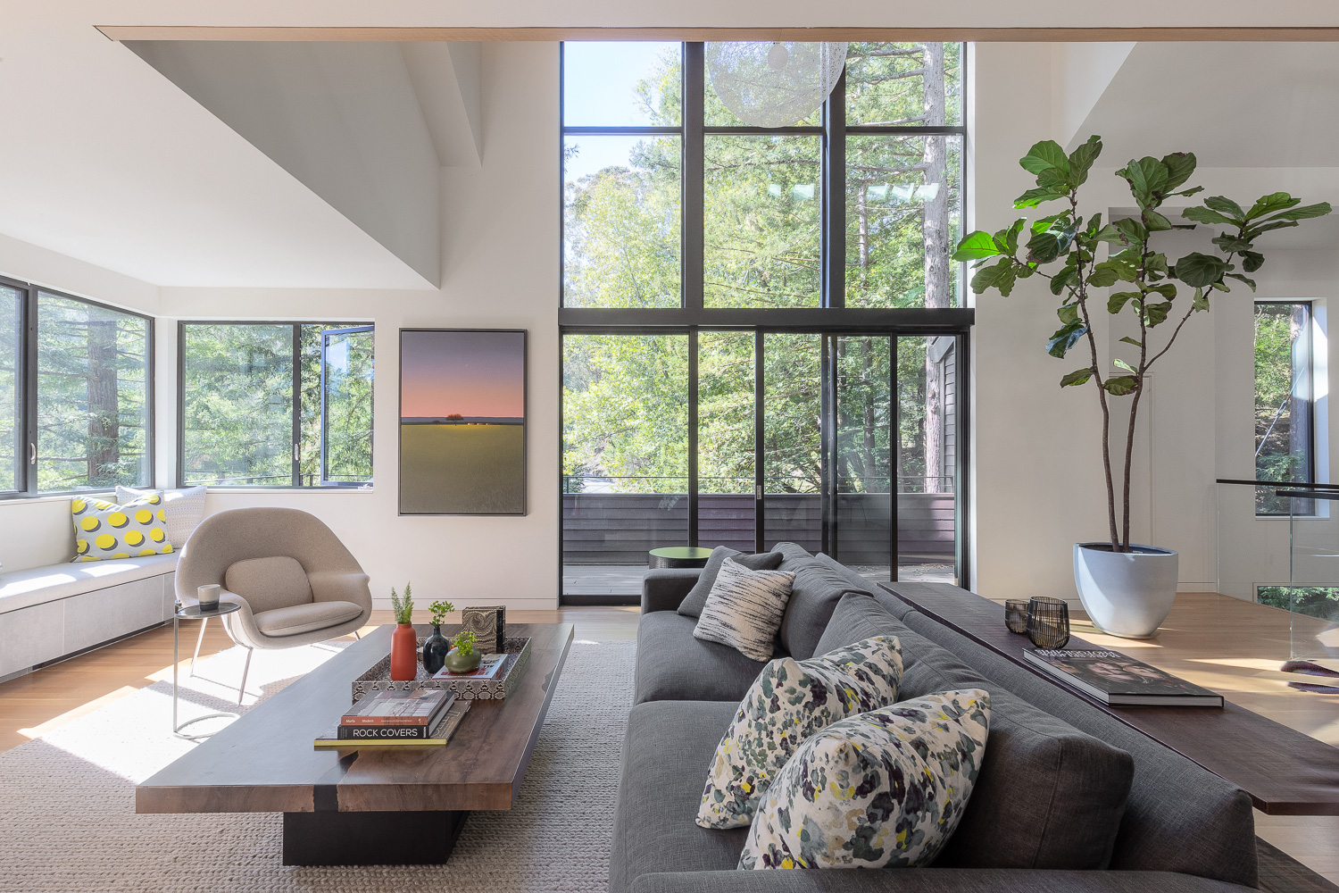 For the den, a gray sofa from Rowe Furniture— decorated with throw pillows upholstered in fabric from Romo—is set in front of a low, wood coffee table from Loggia Showroom. The woven rug underneath is from Jaipur Living.