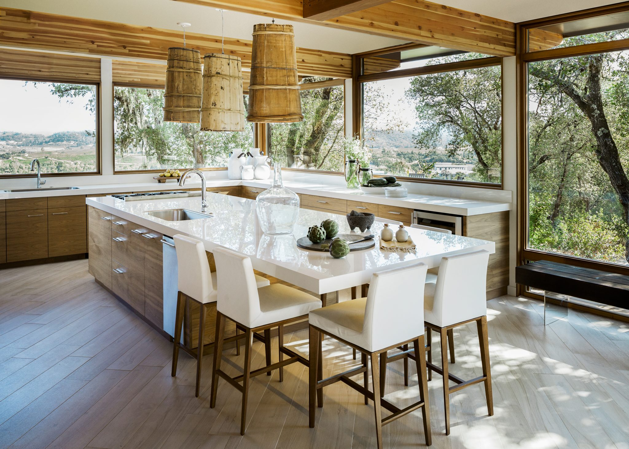 Manyfurnishings in the homepossessa unique history—for example, these one-of-a-kindpendant lights from Wildflower Organicswere crafted from Tibetan carryalls originally used to transport water. Karma Dog Construction built both the cantileveredporcelain countertops andbookmatched black walnut cabinetry, while the chic stools set around the kitchen island are from Calligaris.