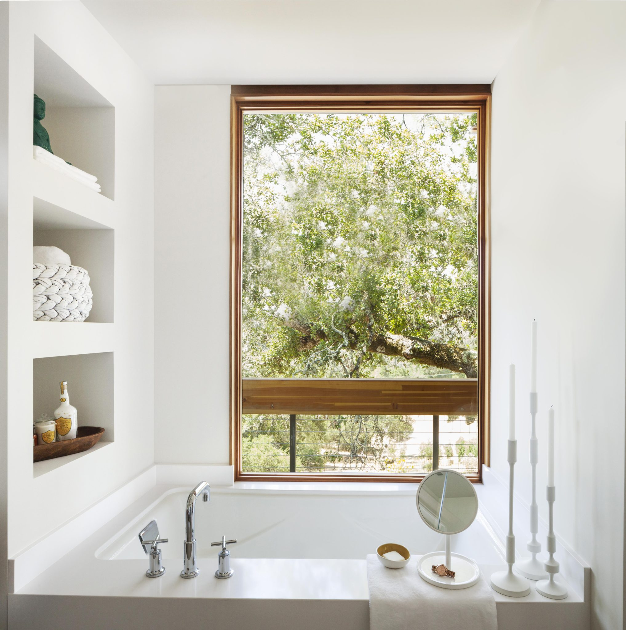 A tall window near the tub brings the outdoors into the bath. The faucets are from Kohler, and the candlesticks are from CB2.