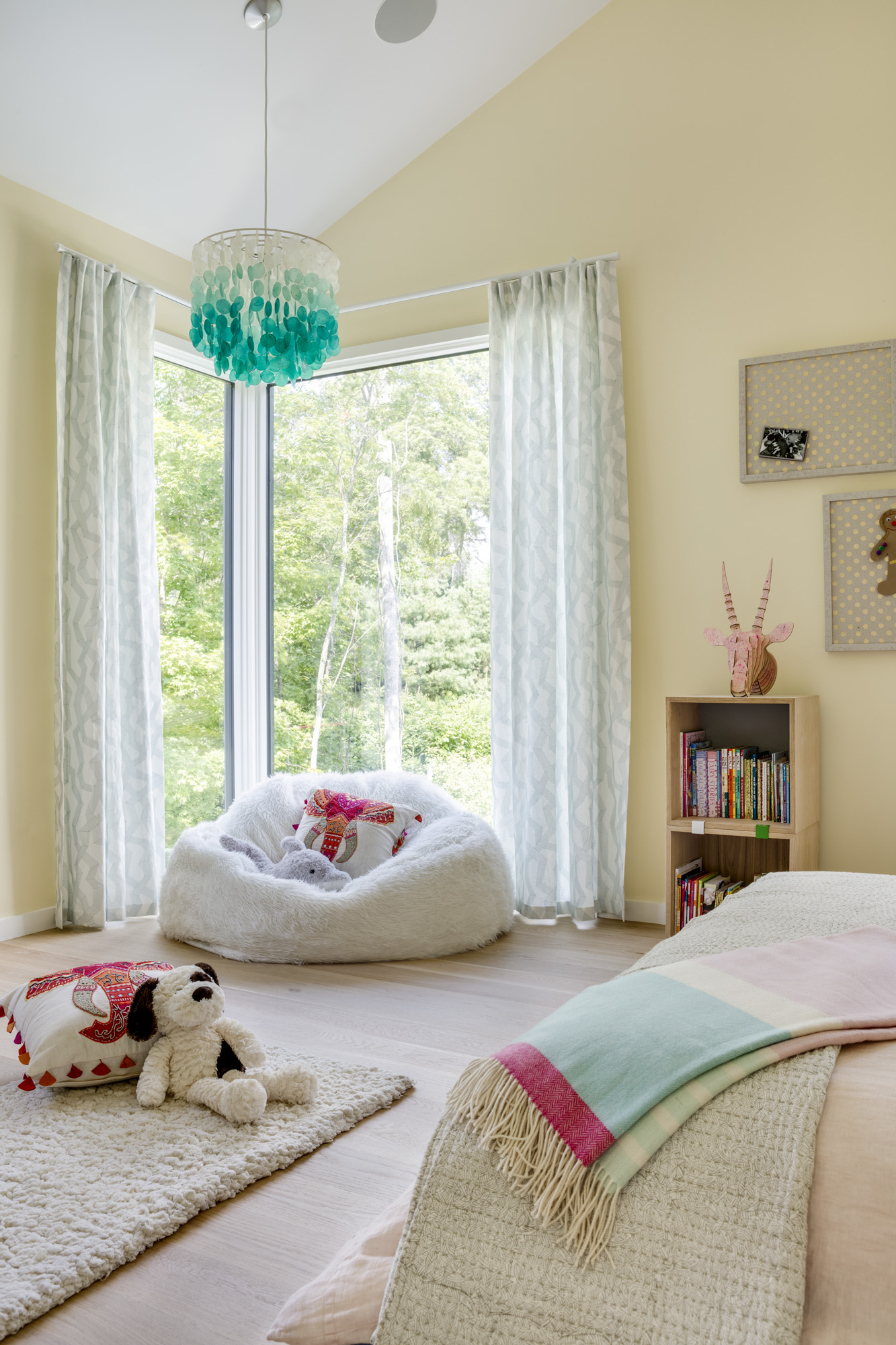 The turquoise and pink color palette flows seamlessly into the girl's bedroom. Curtains and shades from The Shade Store help control natural light, and the blue pendant light is from Pottery Barn.