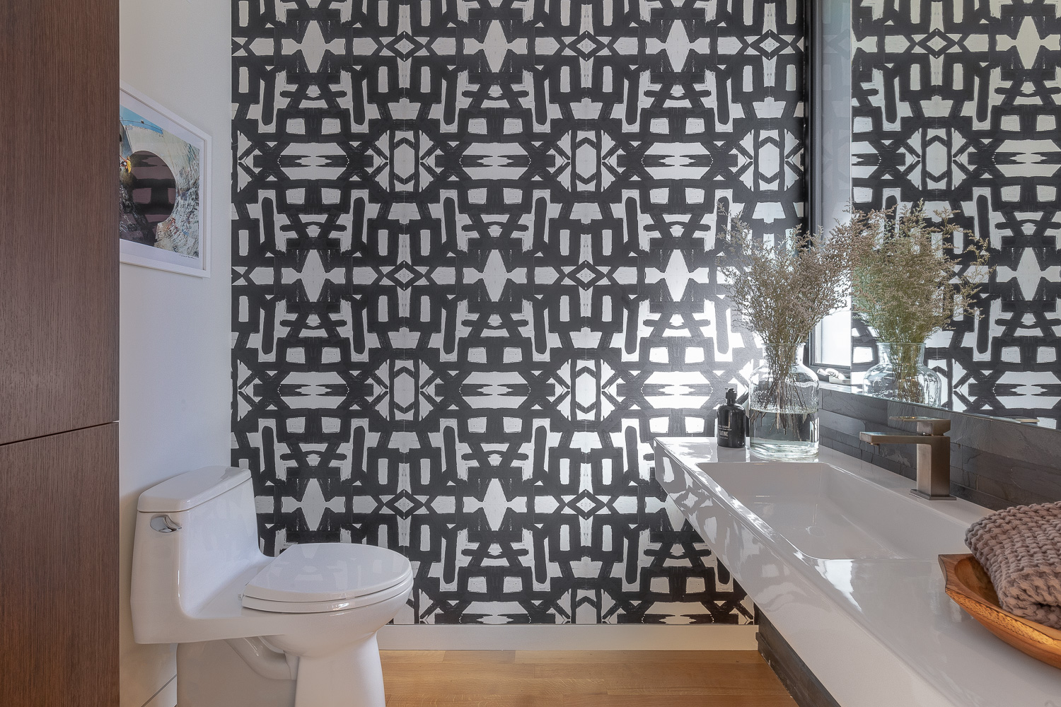 In another powder room, a high-contrast, geometric wallpaper from Lindsay Cowles offers excitement.