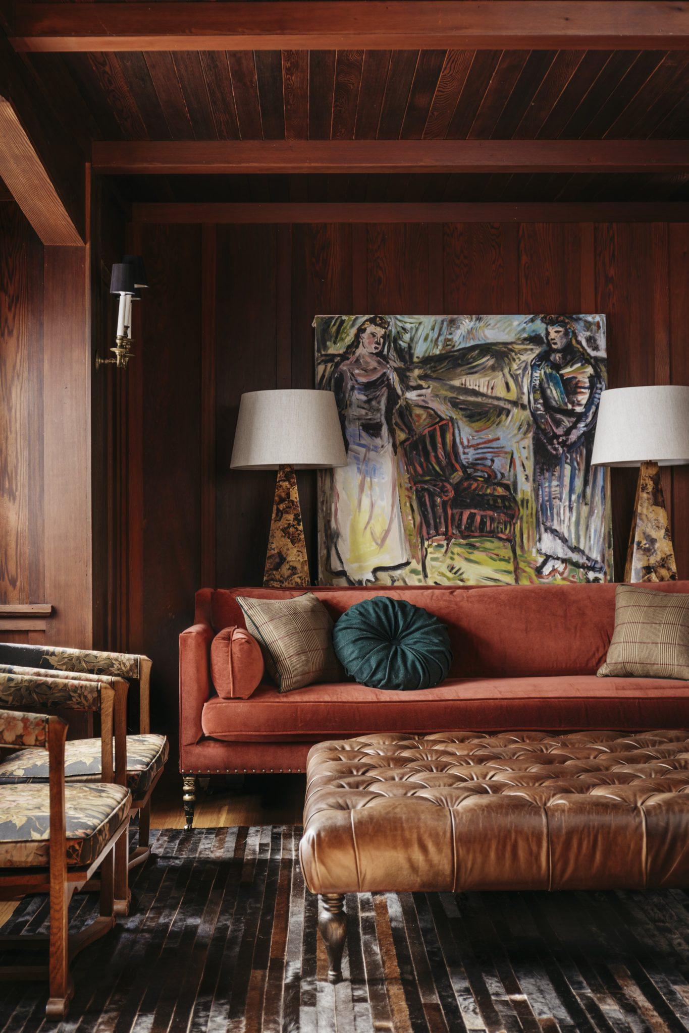 The striped cowhide rug is from Restoration Hardware. Bunny Williams Home designed the pen shell lamps; behind them, a contemporary artwork,Two Graces by Joanne Landis,gives the space an eclectic flair.