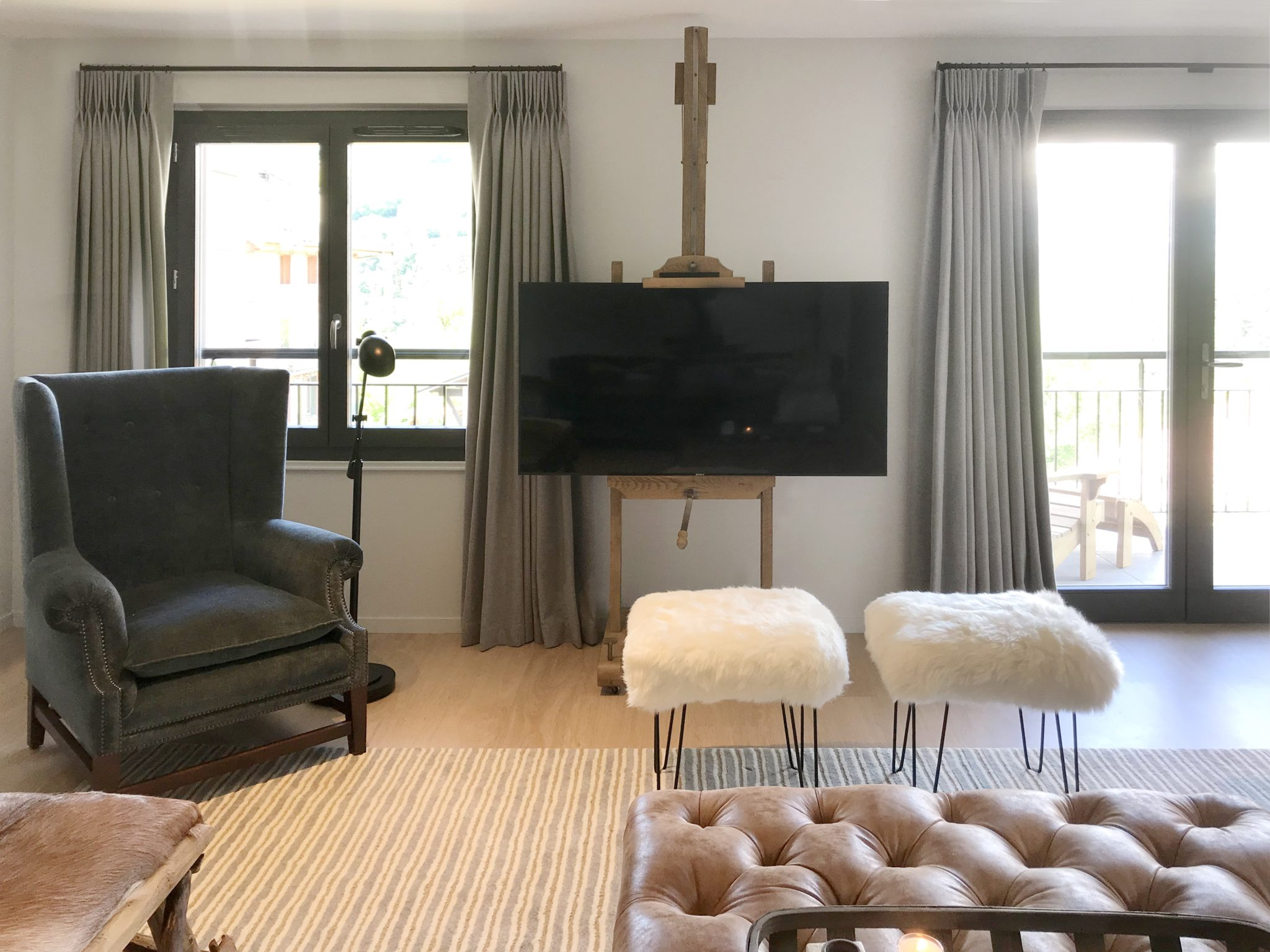 """DECIDE ON THE FUNCTION OF THE SPACE   For multi-purpose rooms that function both for entertainingandentertainment, it may be best to hide the TV. """"We often hide the TVbehind art or wall panels so that it's not on display,"""" says Audrey Carden, co-founder ofCarden Cunietti. """"If the room is solely for TV watching, then we make the seating as comfortable as possible with foot stools or ottomans for extra relaxation."""" When theTV can't be hidden in an entertaining space, make itlook as beautiful as possible. """"In this room we didn't have a wall that lent itself to built-in joinery, so we decided to make a feature of the TV and mount it on an easel."""" Technology becomes art.   A living room and TV area in a French chalet by Carden Cunietti."""