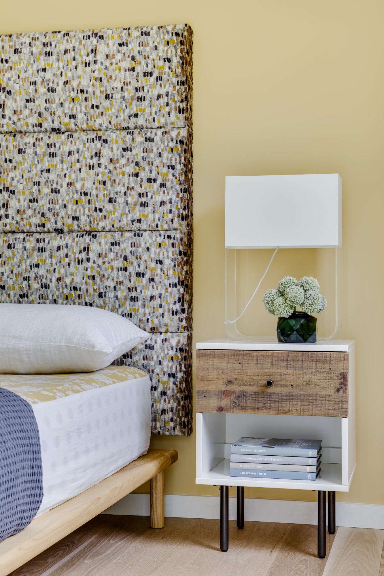 For one of theguest bedrooms, the designers styled a Lusso headboard featuring dotted, earth-toned fabric from Romo with rustic minimalist nighstands from West Elm. The bed was sourced from Wilbur Davis Studios.