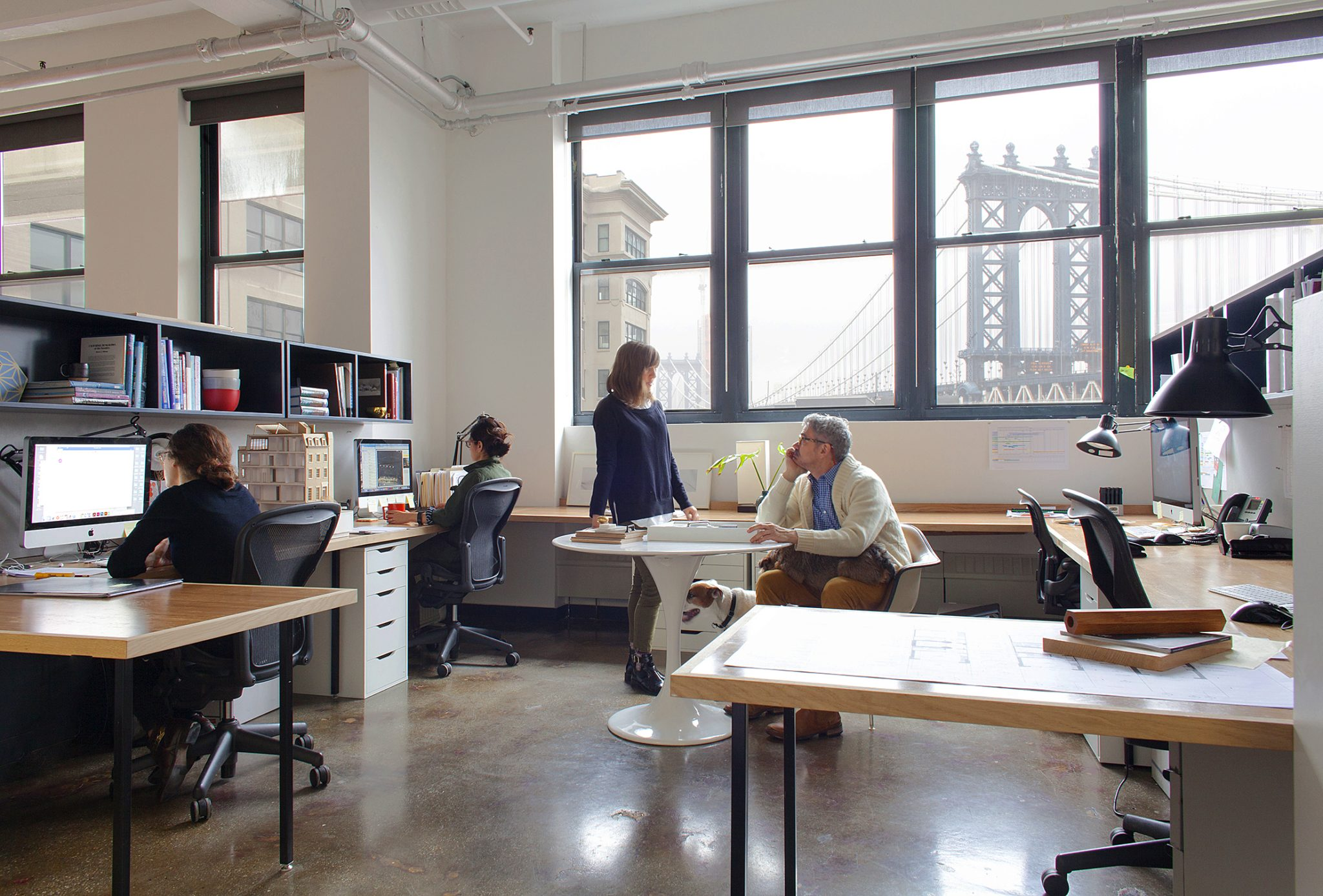 """CWB Architects   Brooklyn, New York   """"In 2017 we relocated our DUMBO office from the 12th to the eighth floor of 45 Main Street, a converted factory building. Our team of architects had outgrown the existing space and the design had begun to feel dated. Our office has always been a hub for Brooklyn creatives, with sub-tenants occupying any space not used by the firm. The new space needed to accommodate this shared space while allowing for growth within our own firm. The result is an artfully designed workplace that incorporates an open plan for our designers, office alcoves for sub-tenants, conference rooms for private meetings, and a kitchen for communal meals and conversing across the many disciplines that inhabit our workplace. Our office currently provides a home for ten small Brooklyn businesses, totaling a collective of 40 individuals working for Brooklyn companies, sharing space and ideas throughout our workdays.  """"A foundation of our commercial practice envisions the workplace as a 'mini-city.'Planned neighborhoods of desks connect to """"streets"""" organized around public plazas with varying degrees of importance relative to the kind of programmed gathering activity. Our own office demonstrates this experience to clients and helps us learn first-hand what works and what could be improved. The framework helped us satisfy all our program needs while designing a space that promotes creativity and a sense of community.  """"The functionality of our design manifests in the separation of public and private spaces. Communal areas for meeting and eating are situated toward the entrance to the space and the interior of the building. Our individual work stations are located at the perimeter of the space, buffered from the entrance and accessible to beneficial natural light and air. Color blocking provides visual identifiers to differentiate types of spaces, signifying separation in our open-plan office.""""  —Ward Welch and Jason Boutin, CWB Architects"""